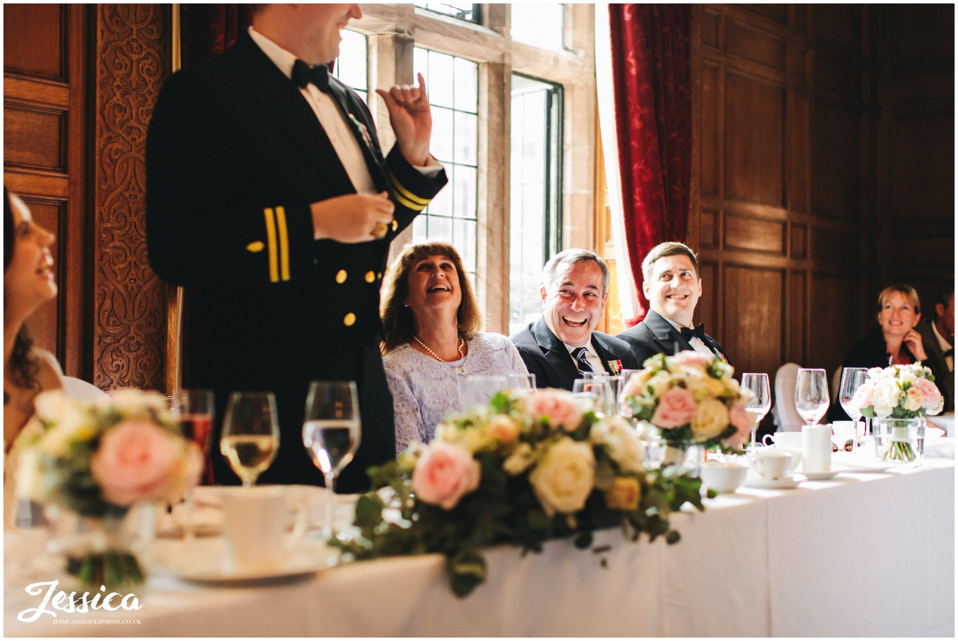 the grooms family laugh sitting at the top table