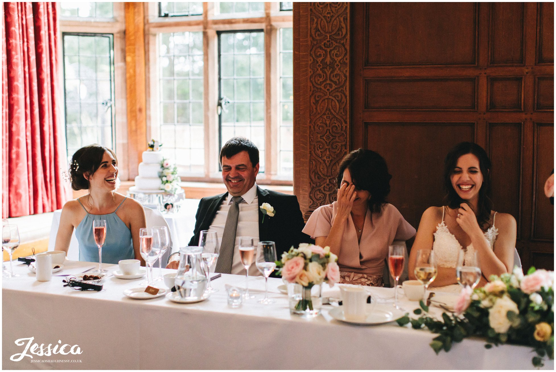 the bride & her family laugh during the best man's speeches