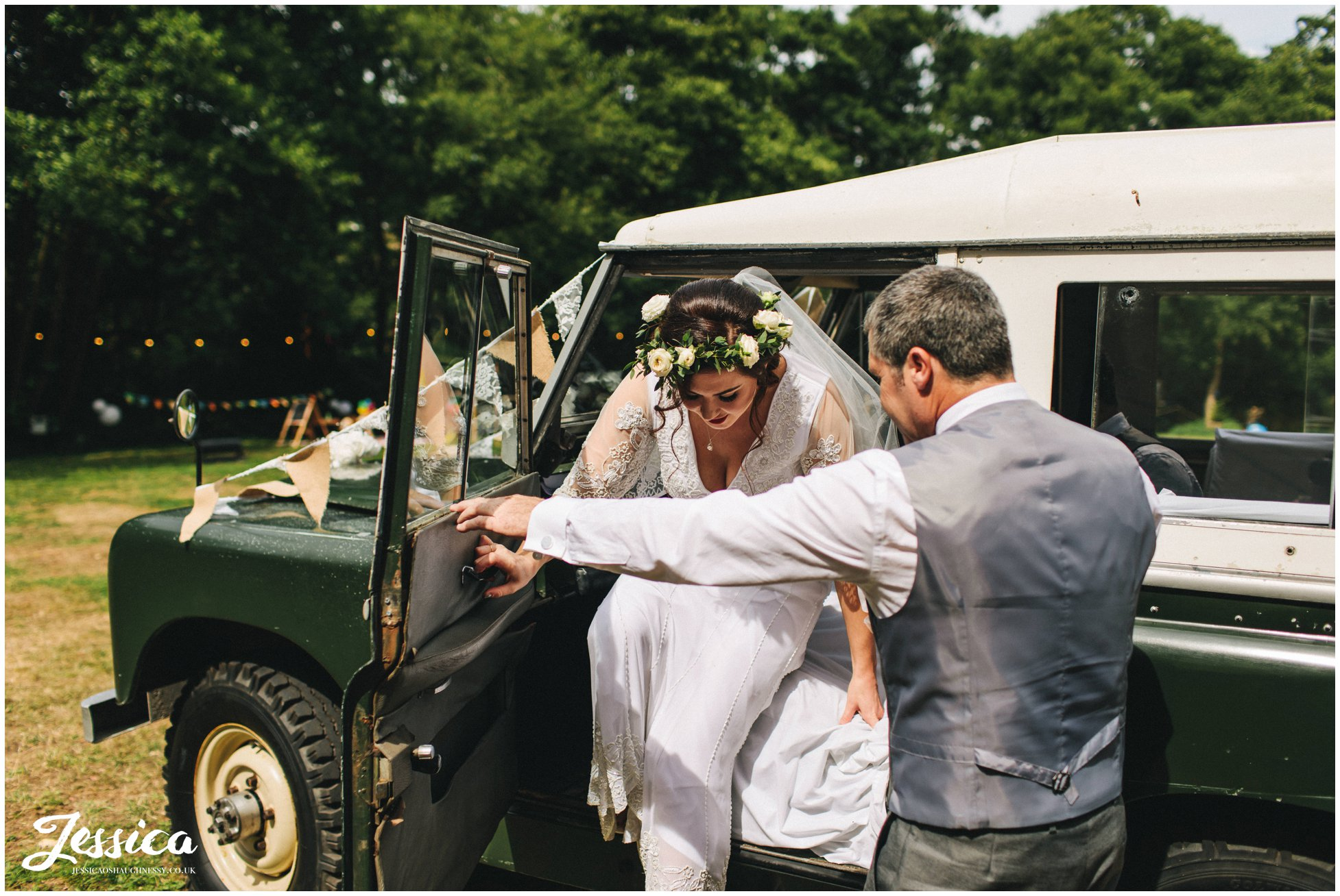 father of the bride helps his daughter out the wedding car