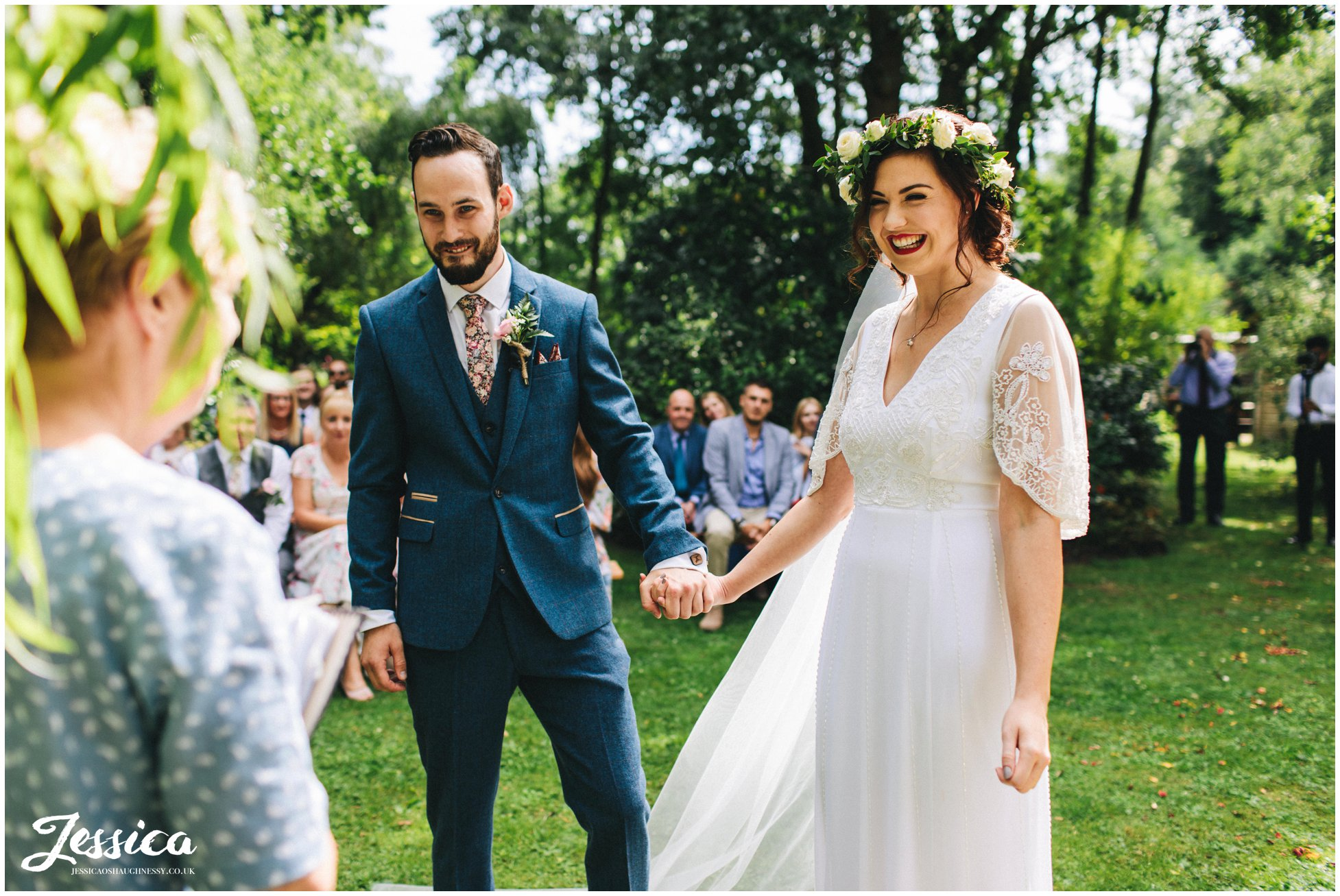 the couple hold hands during their stonyford cottage gardens wedding ceremony