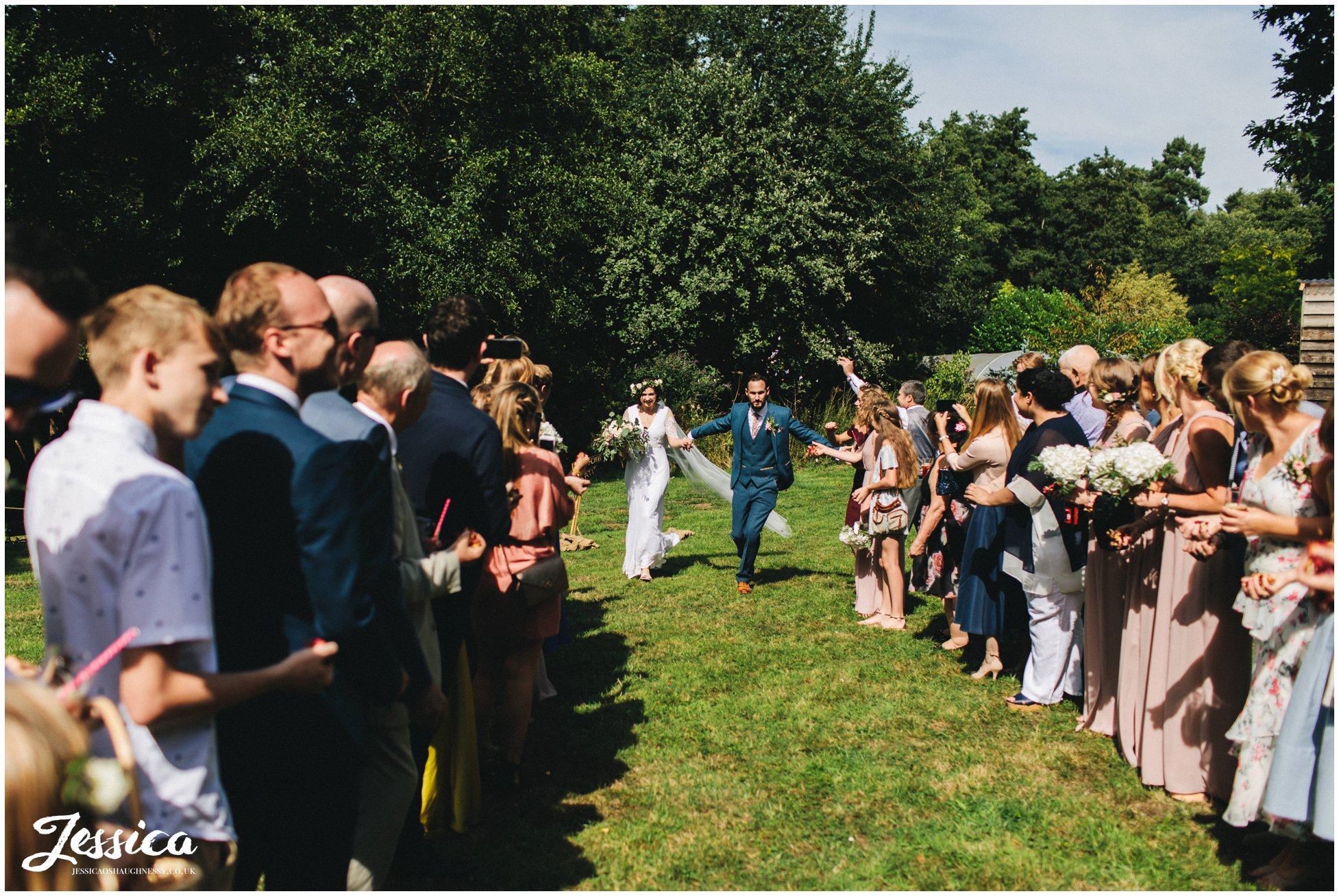 the bride and groom take a run up for their confetti photograph
