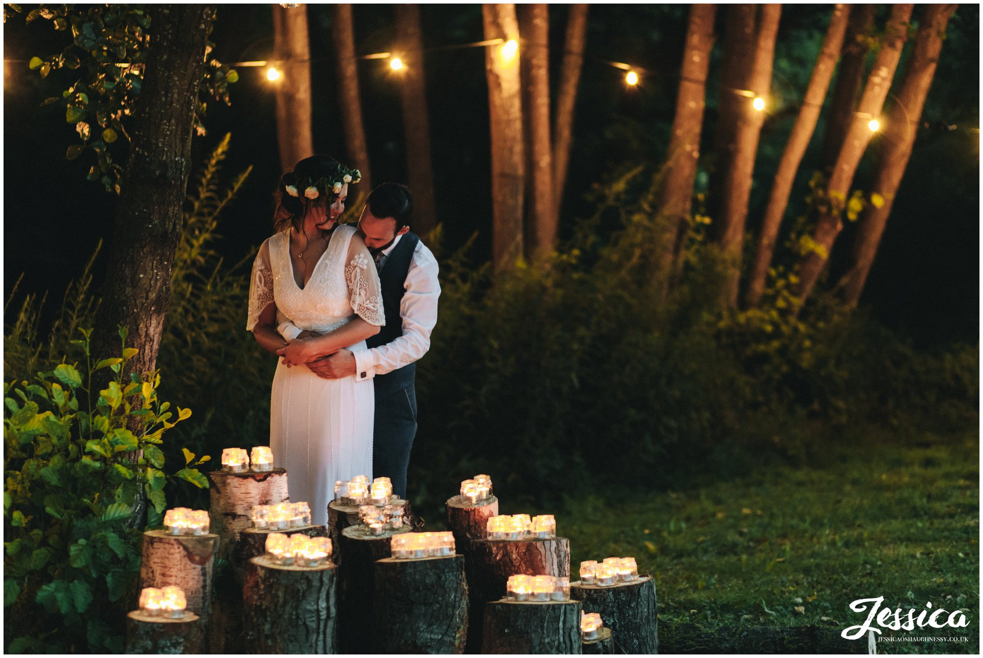 newly wed's embrace in front of lit candles as the sun goes down