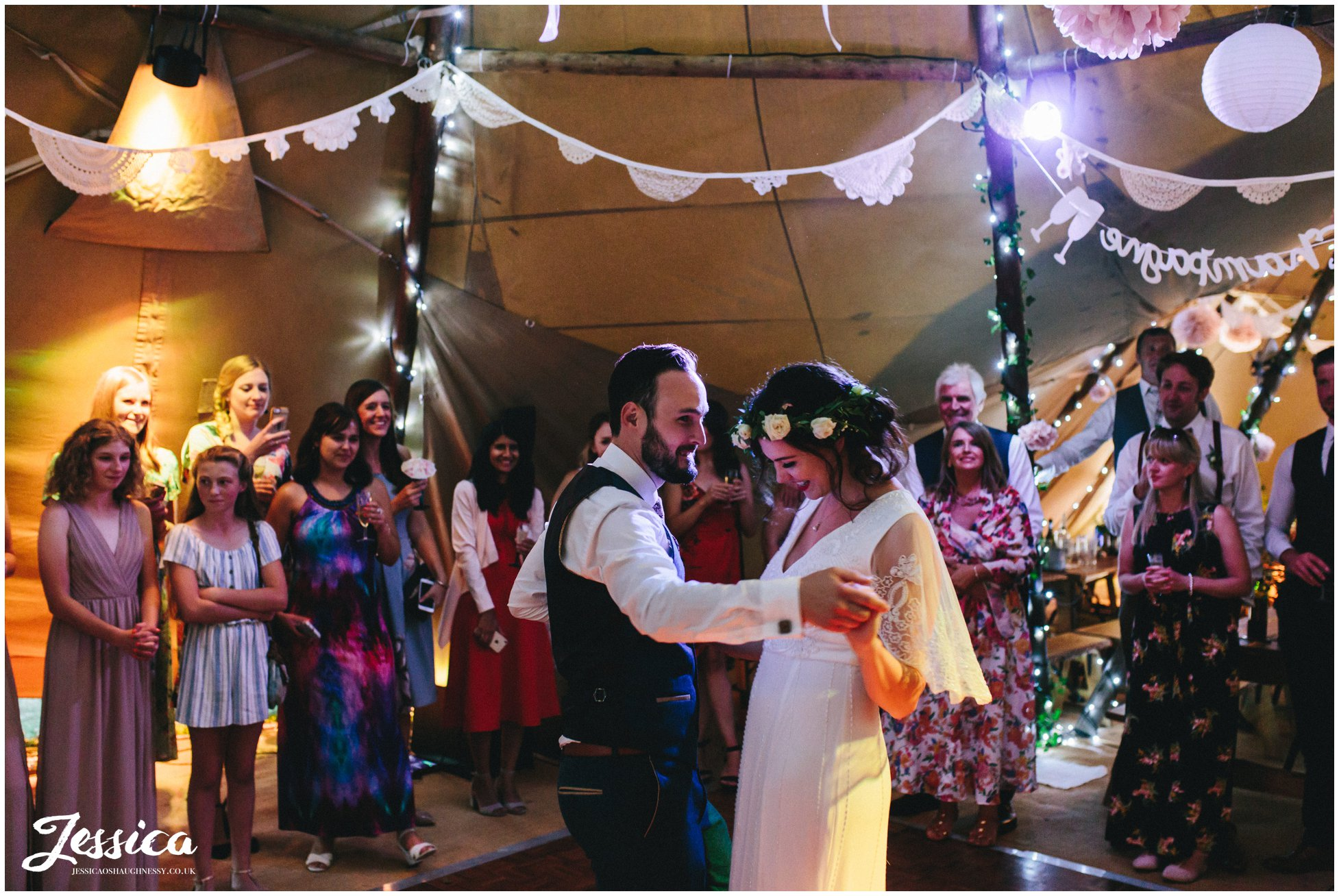 couple share their first dance together in the tipi
