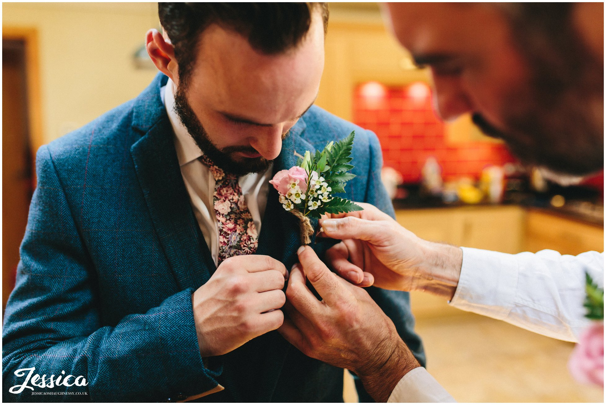 the groom's button hole is pinned on his jacket
