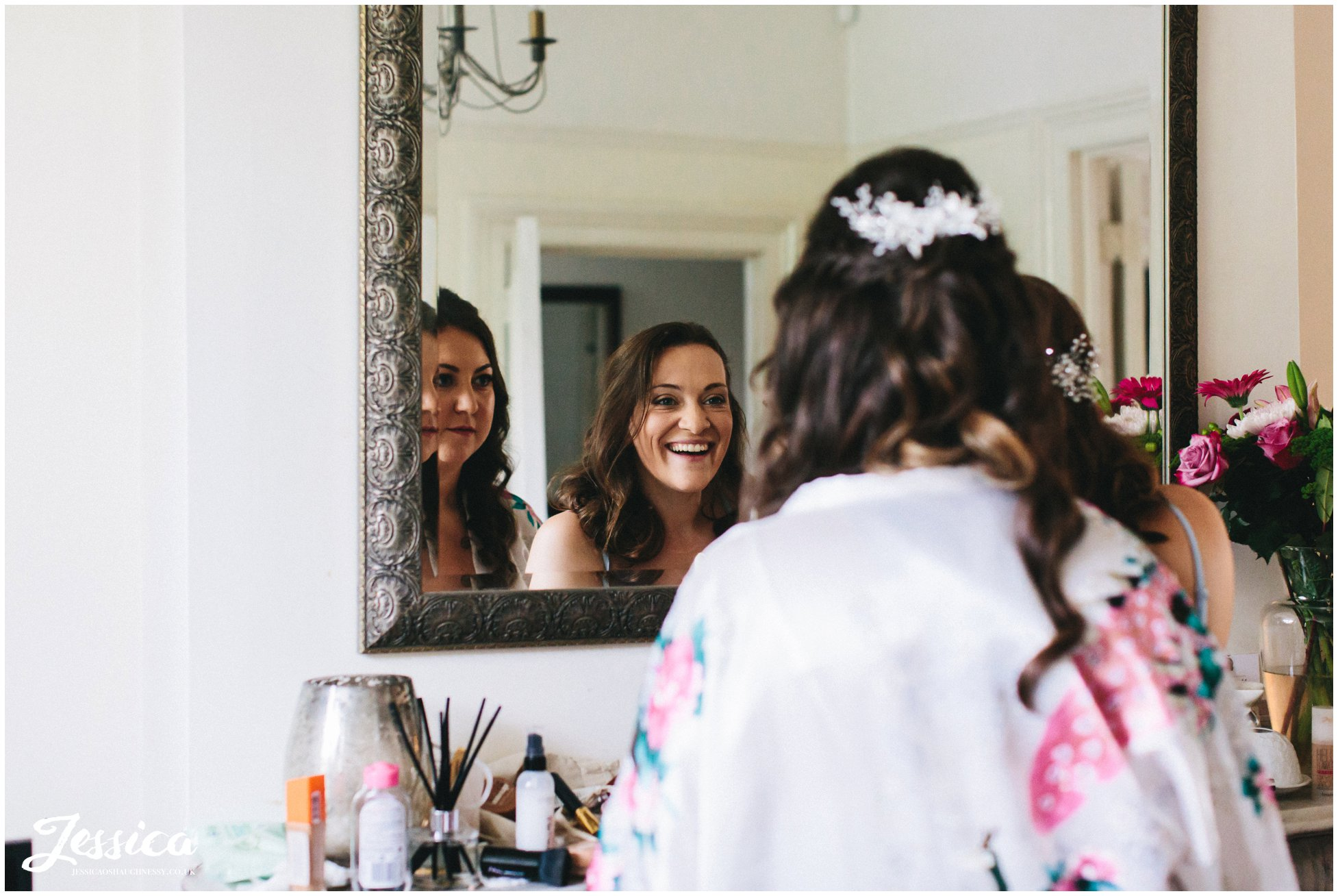 bride admires her make up with her sister