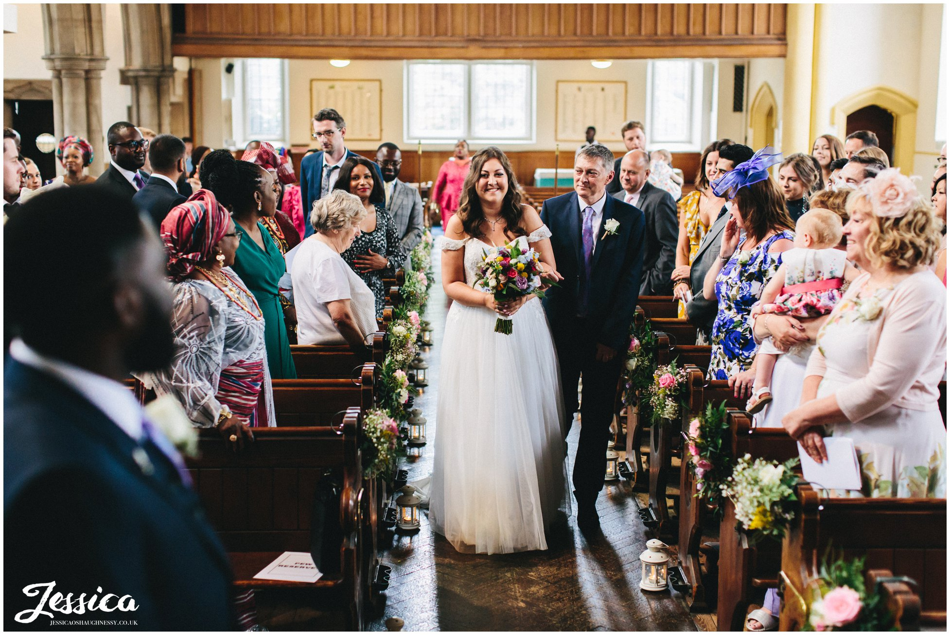 the bride smiles at her groom as she walks down the aisle with her dad