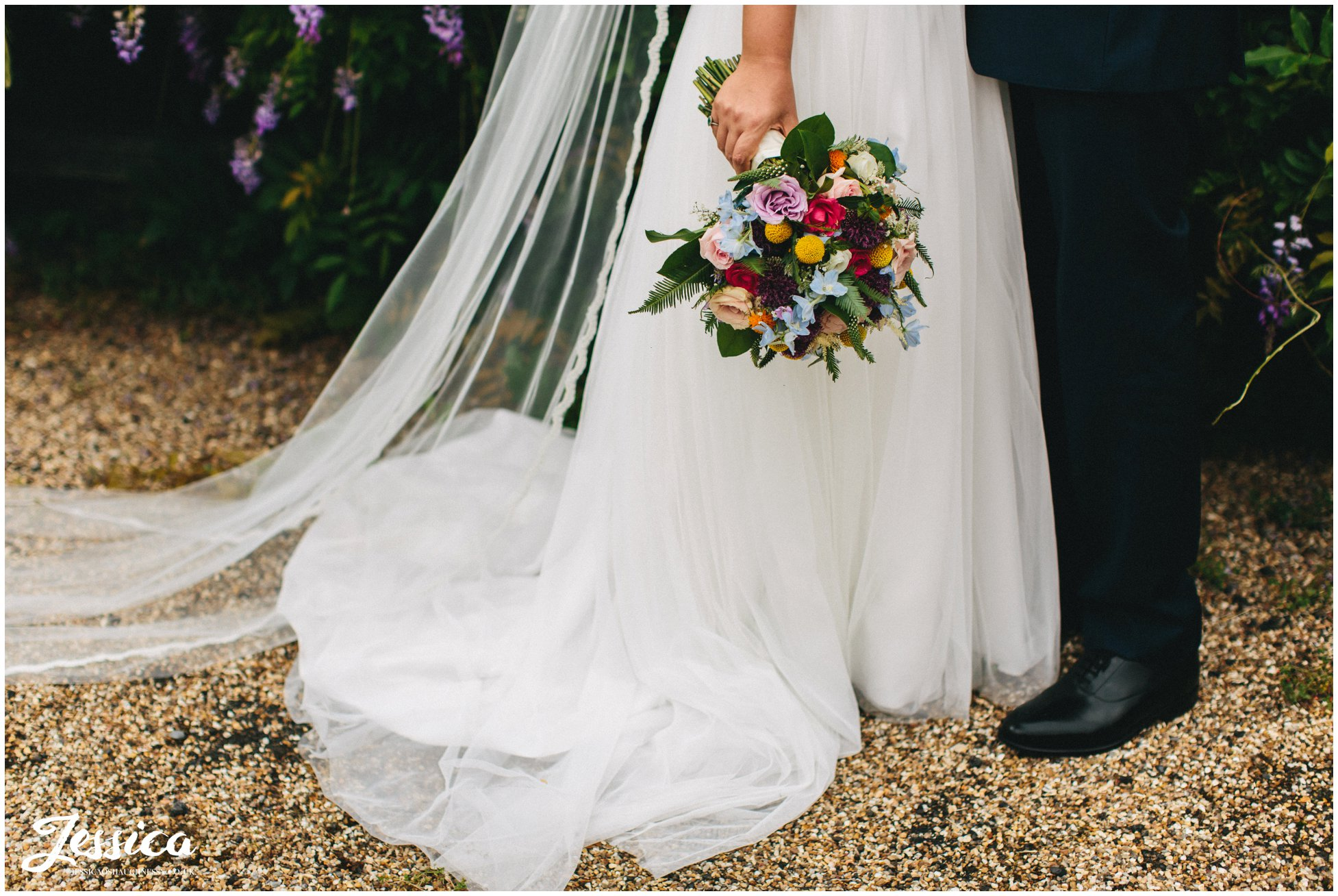 the bride holds her brightly coloured bouquet