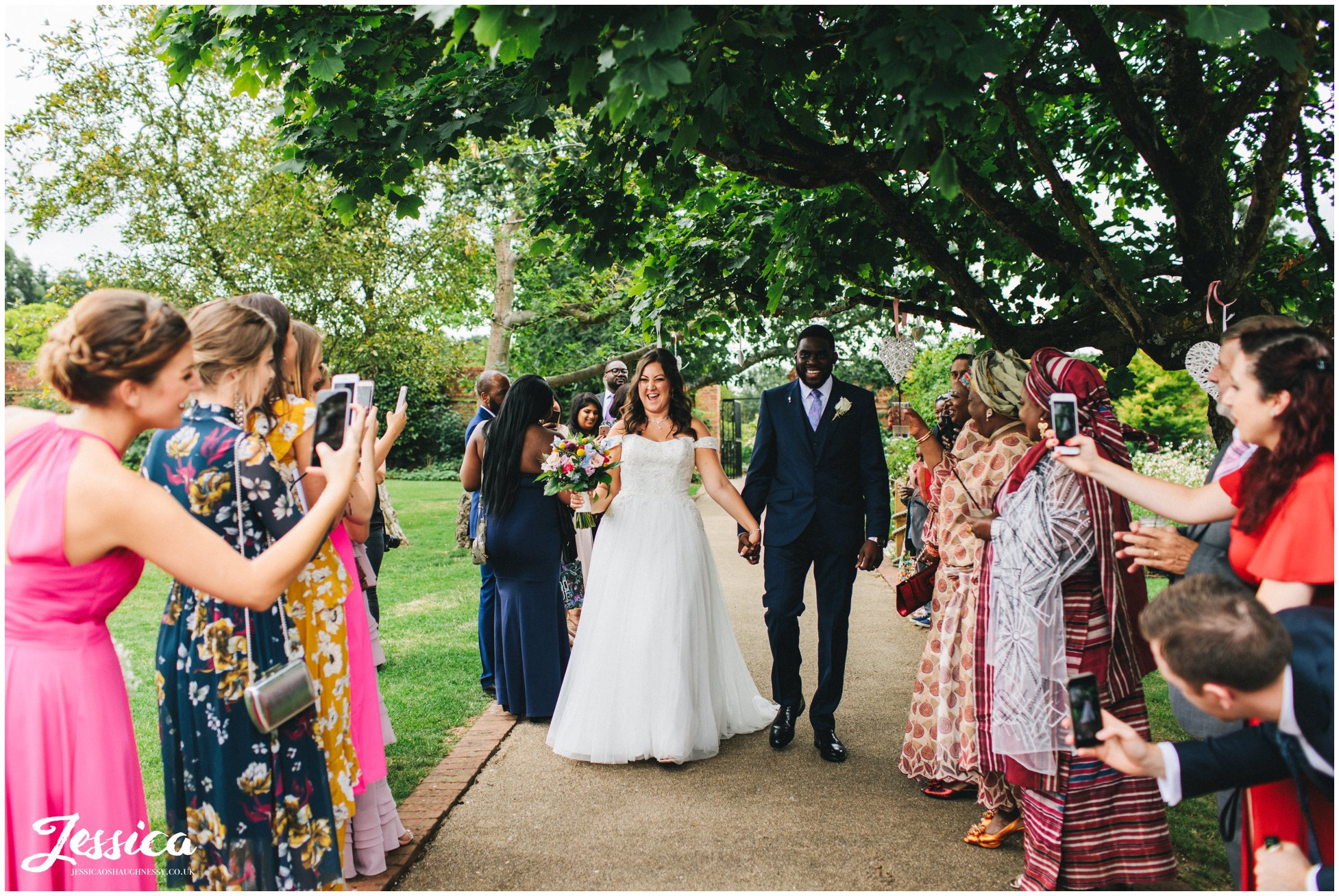 the couple are welcomed in to their gaynes park wedding reception
