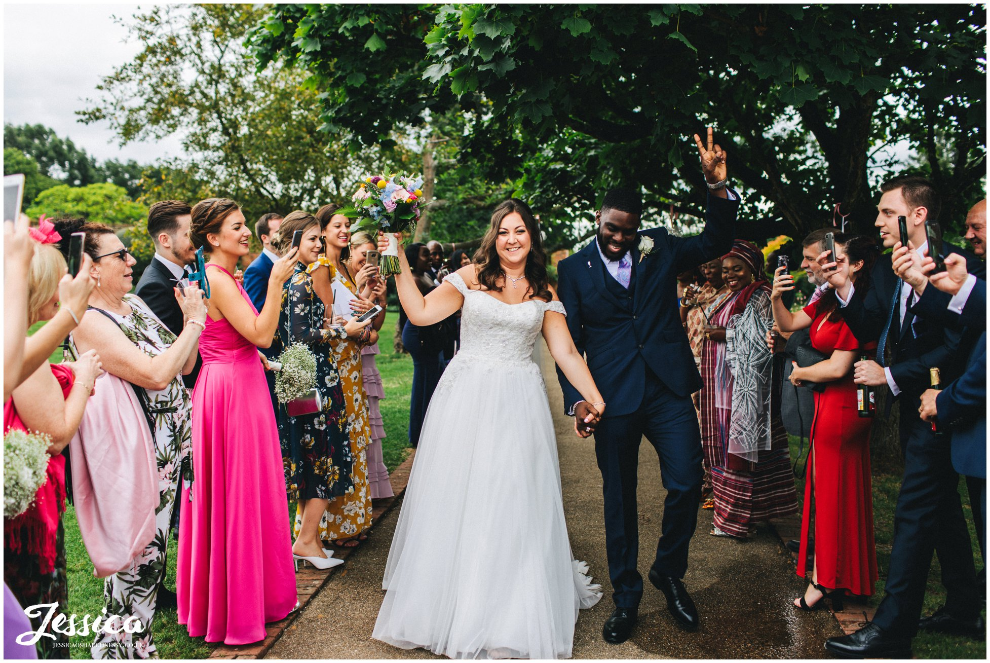 the newly wed's cheer as their guests applaud them