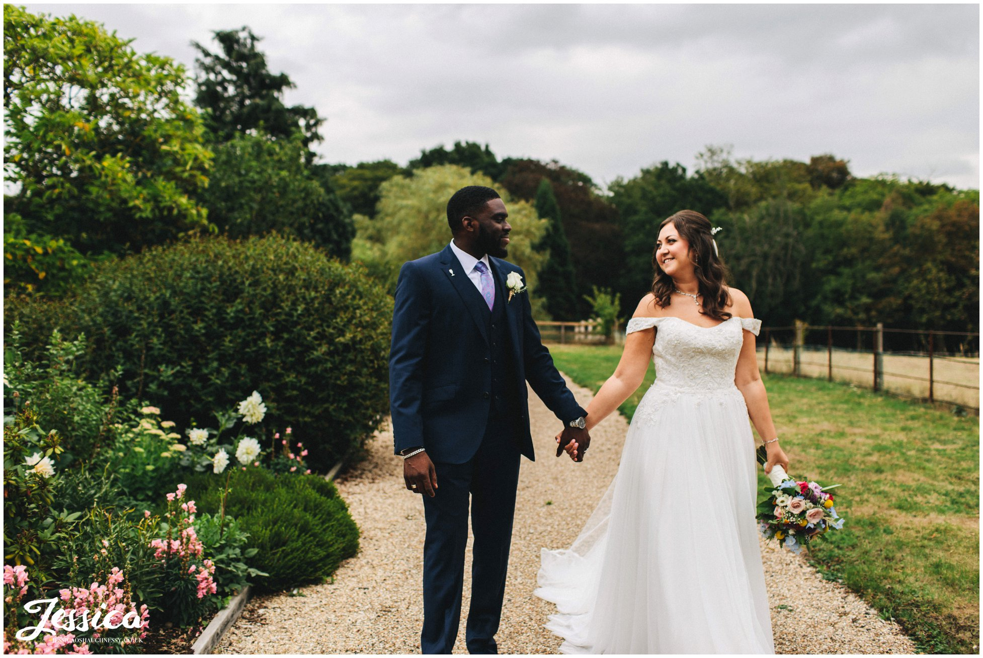 the couple walk through the gardens holding hands