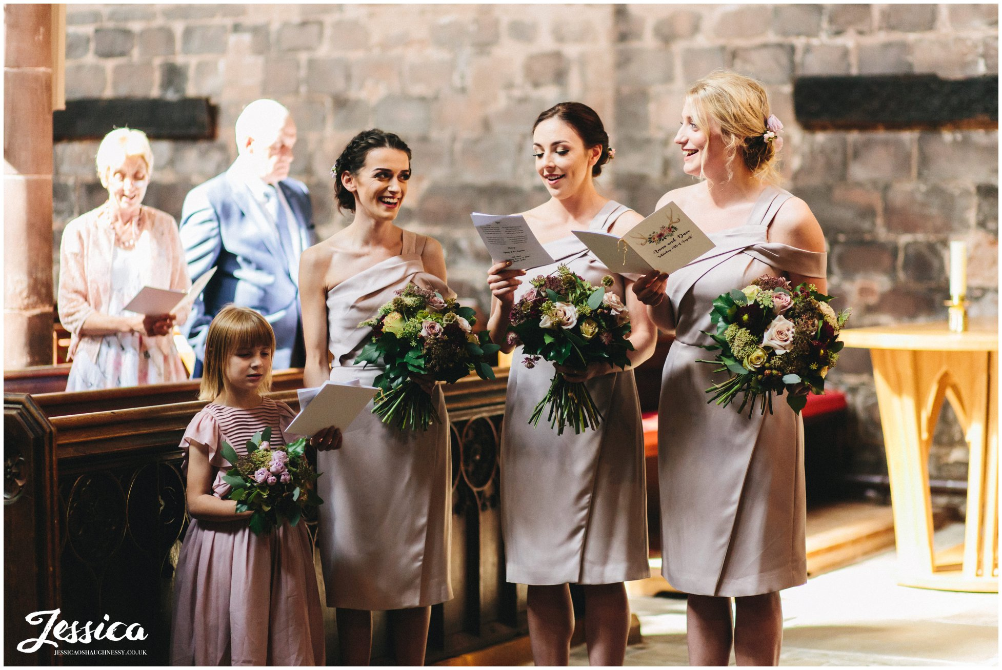 bridesmaids laugh together during the wedding ceremony in cheshire