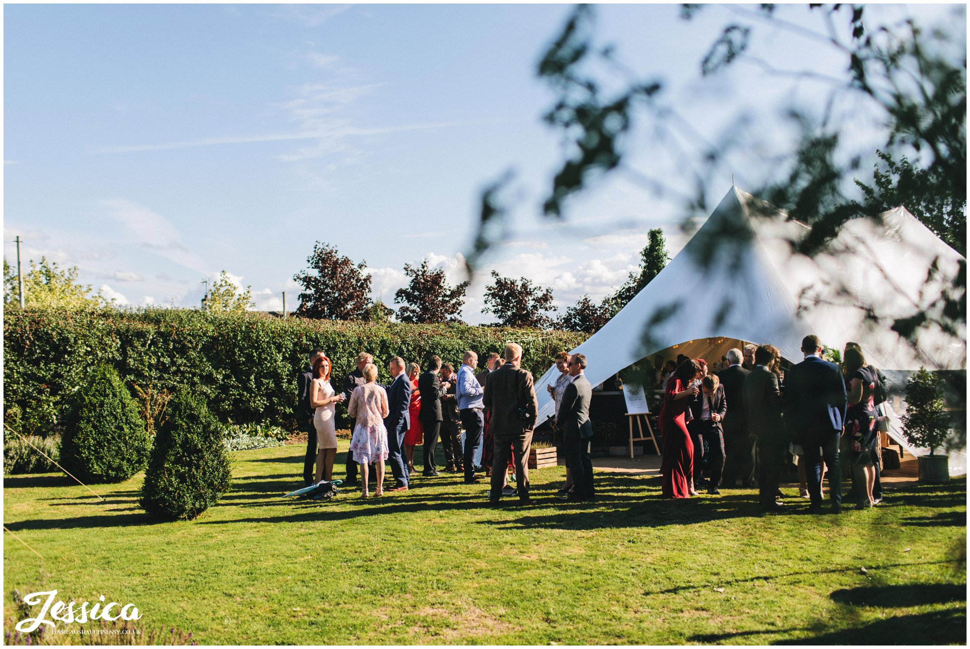 guests enjoy the sunshine at the farm wedding reception
