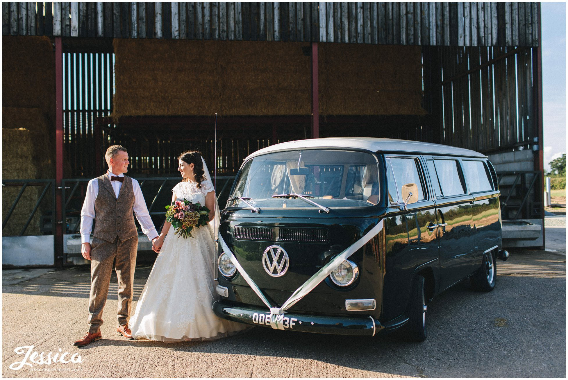 couple pose in front of vintage VW campervan