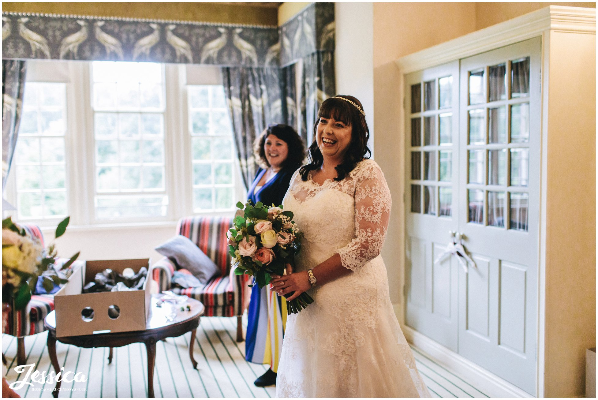the bride smiles as she finished getting ready for the nunsmere hall wedding ceremony