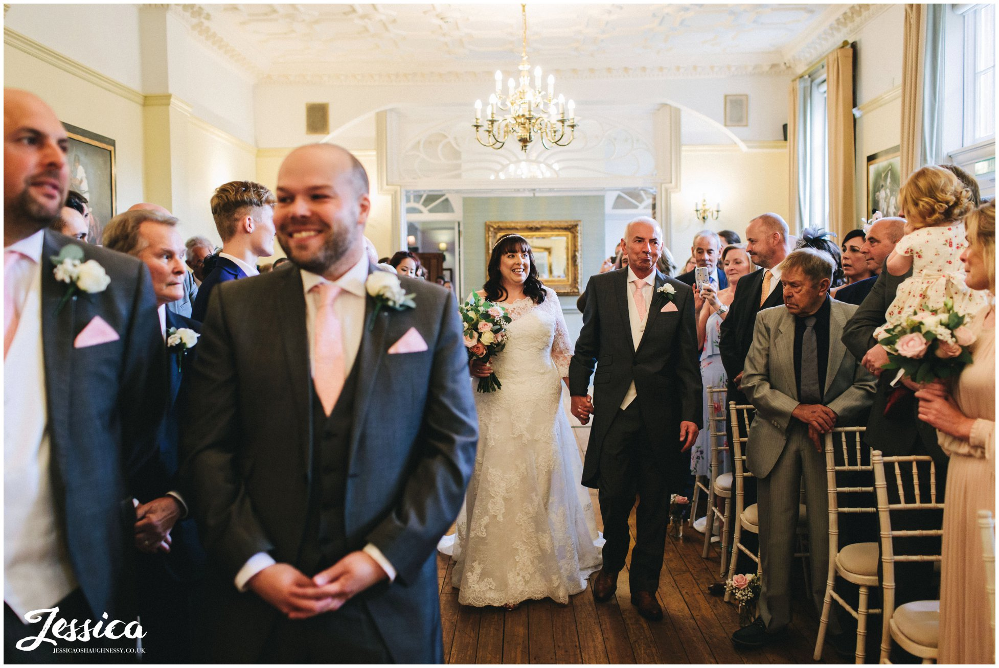 the bride walks down the aisle with her dad at nunsmere hall