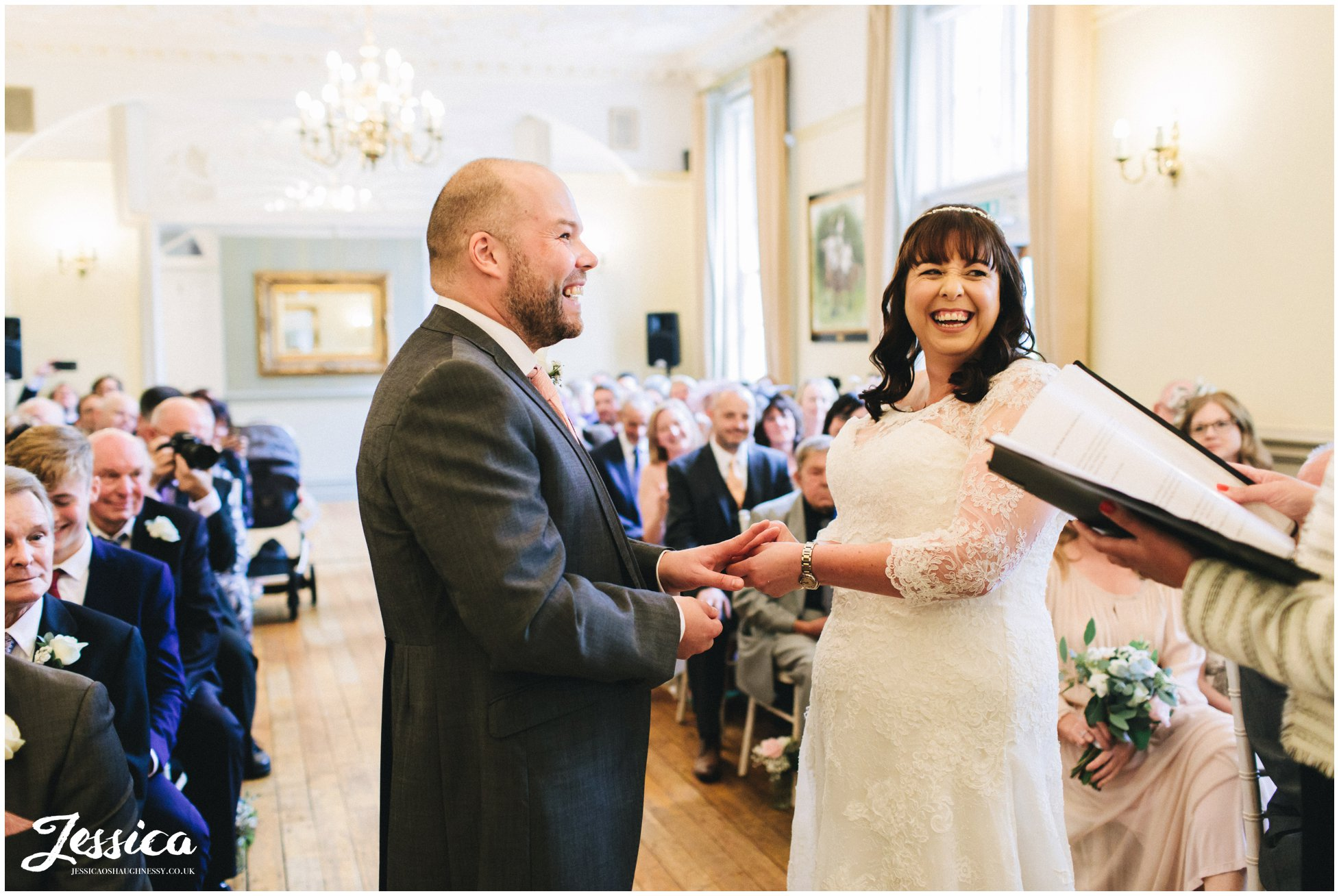 the couple laugh during their wedding ceremony at nunsmere hall