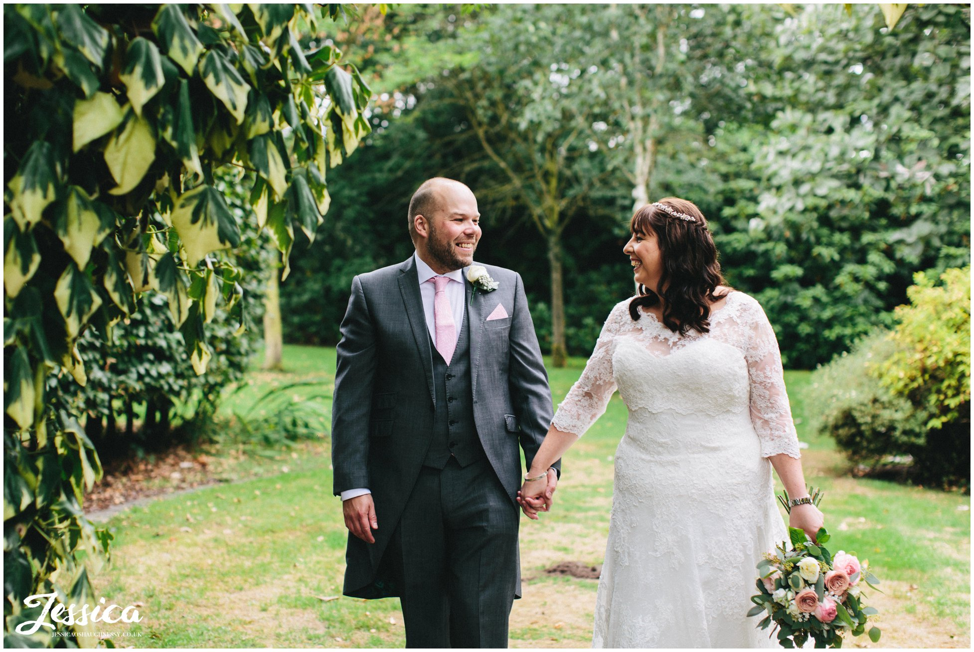 husband and wife hold hands and walk through the grounds of the cheshire wedding venue