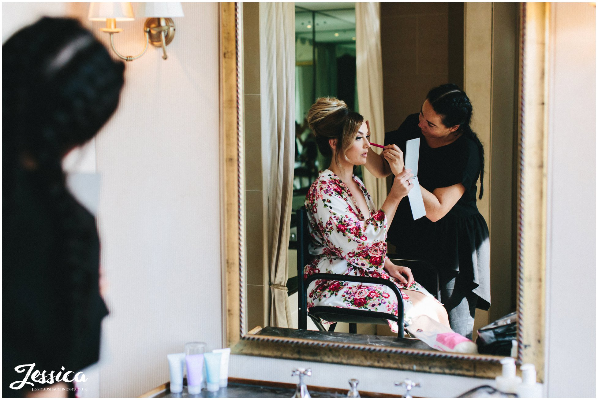 the bride has last make-up touches before the ceremony