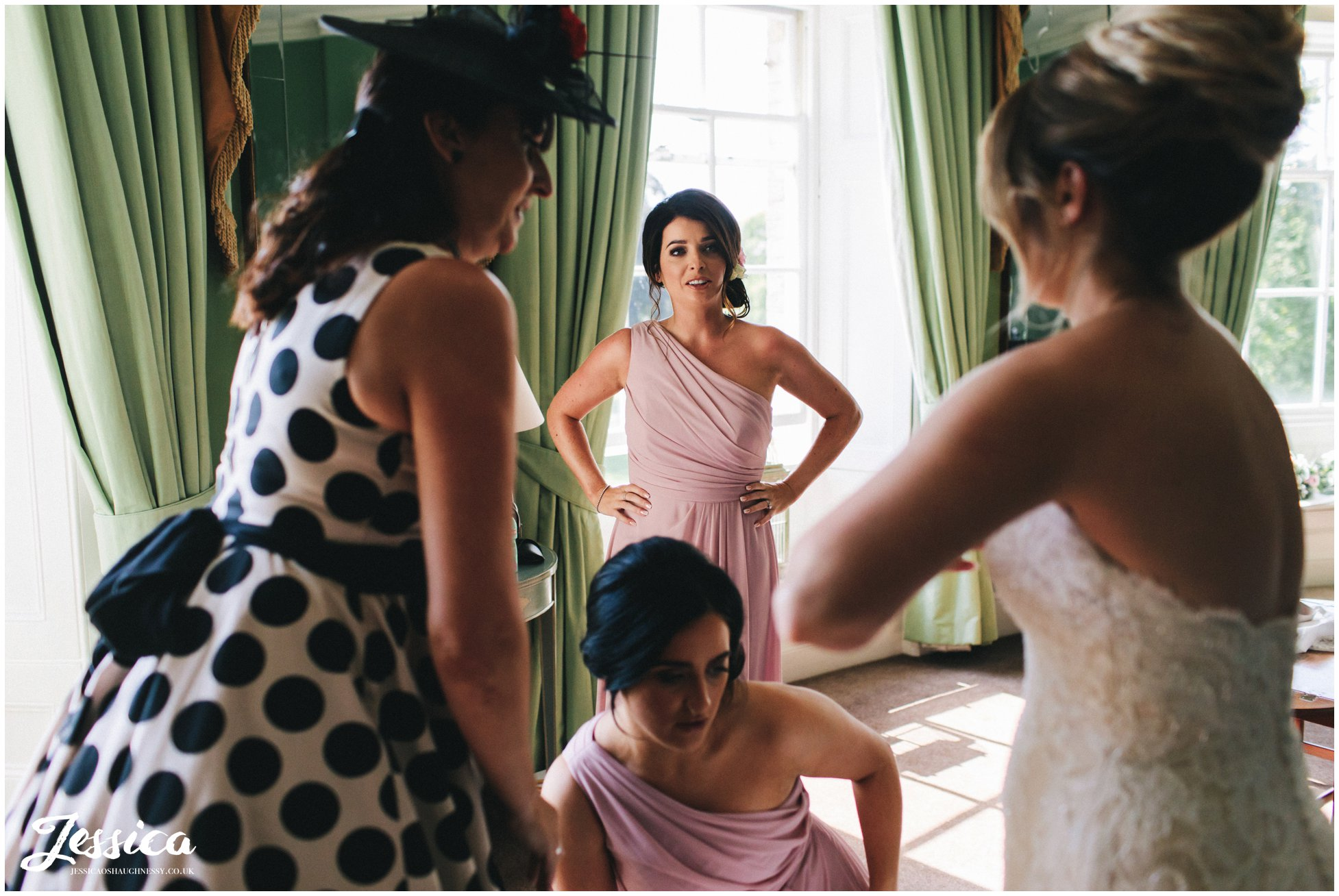 bridesmaids admire the bride as she gets into her dress