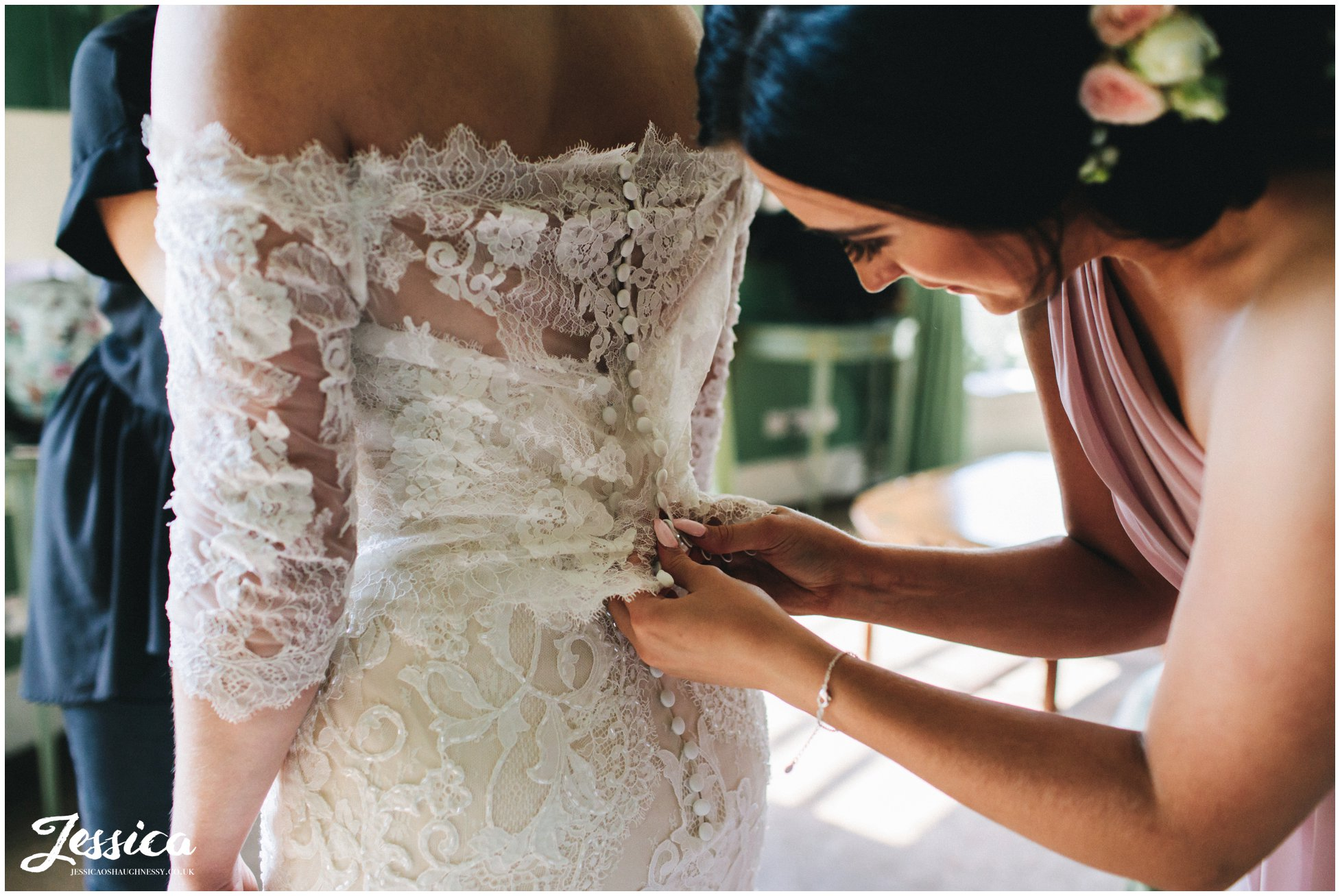 a bridesmaid fastens the brides buttons