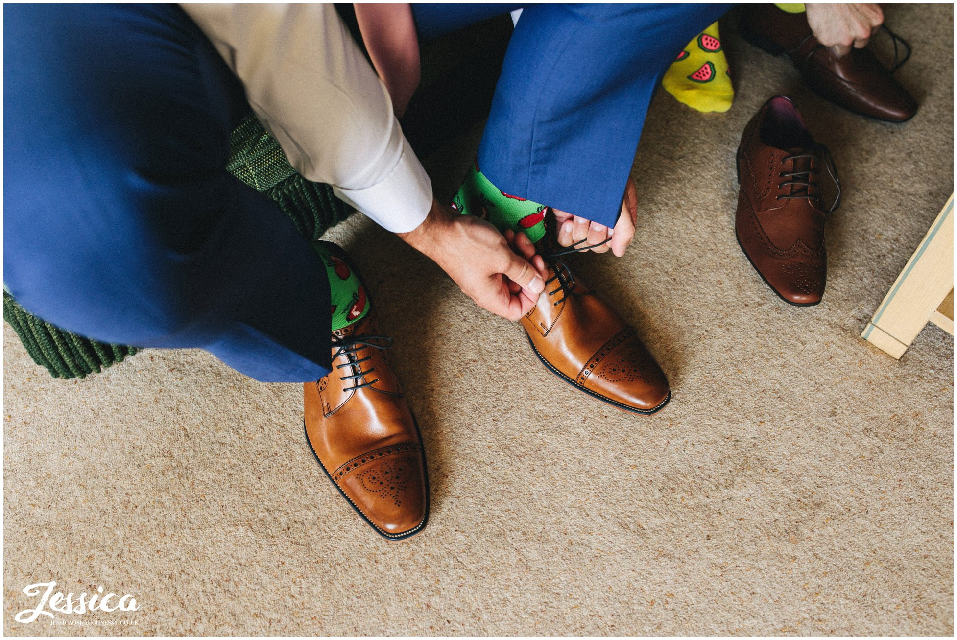 the groom puts on his shoes over brightly coloured socks