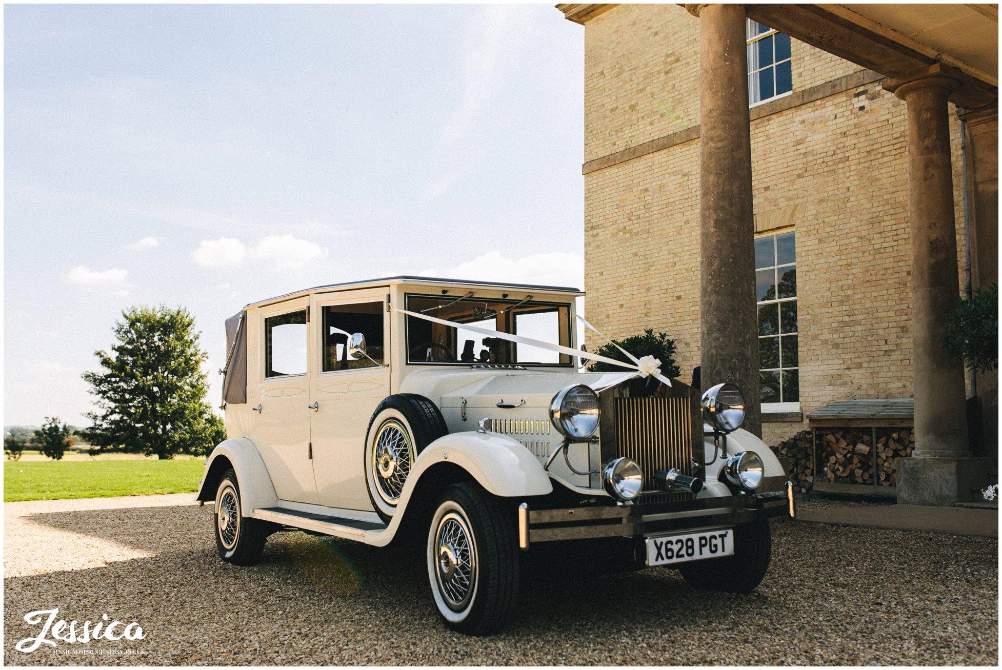 classic wedding car waits outside stubton hall for the bride