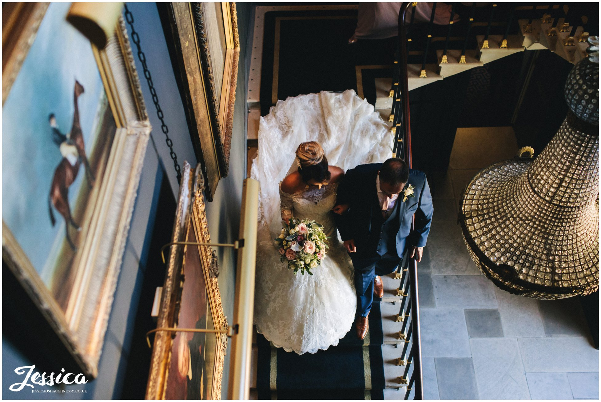 the bride & her father walk down the stairs