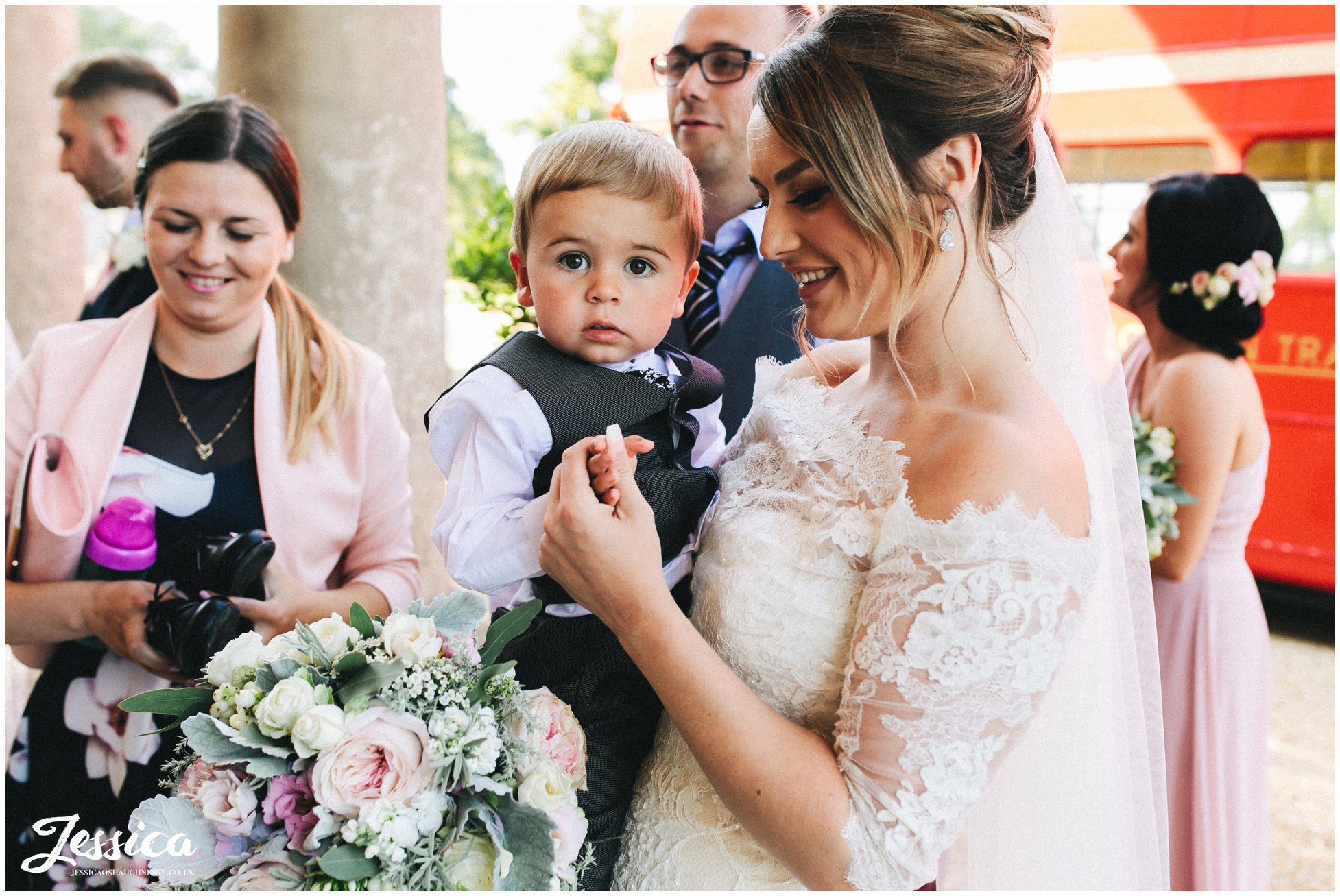 the bride holds a little boy at stubton hall in nottinghamshire