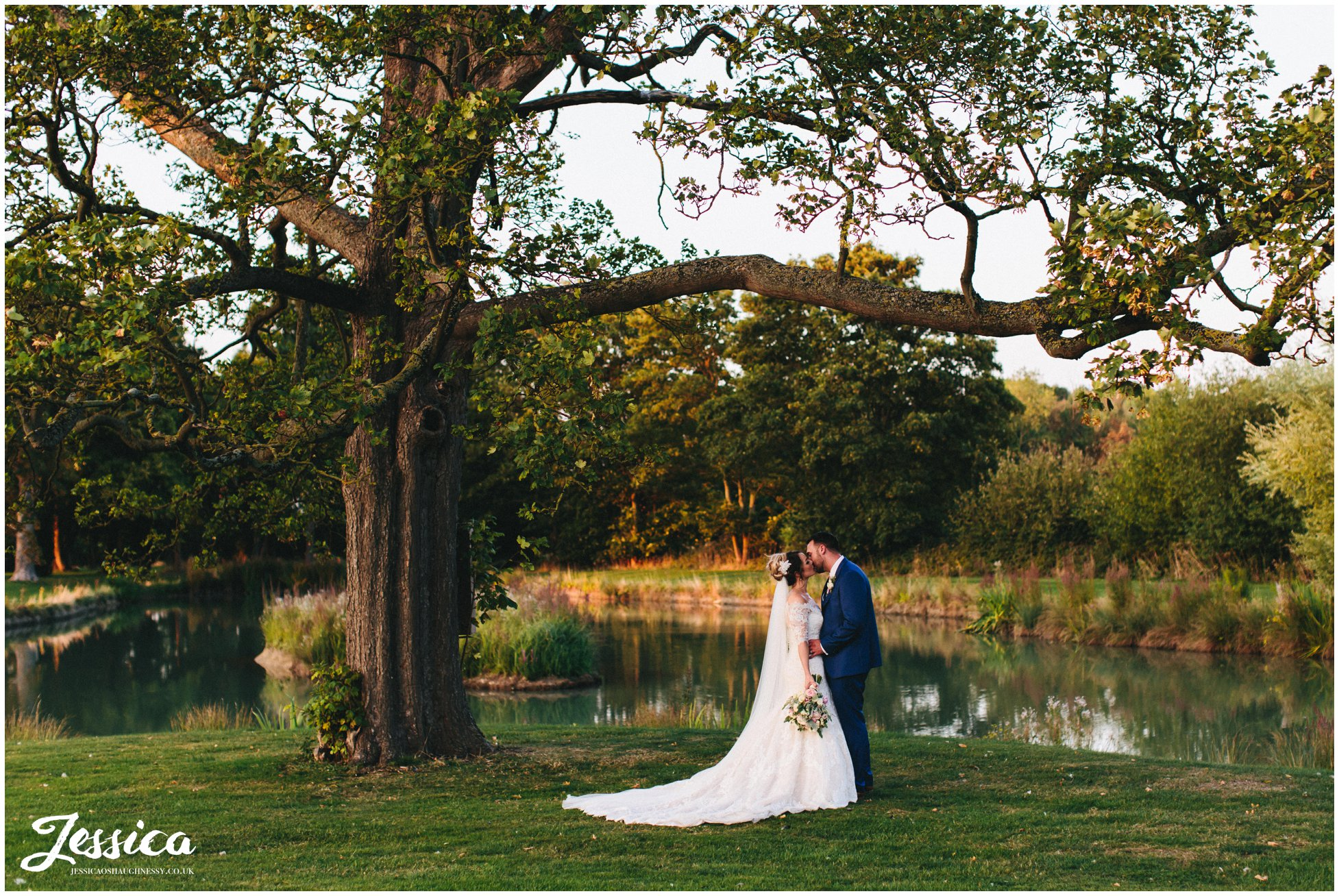 the newly wed's kiss by the lake