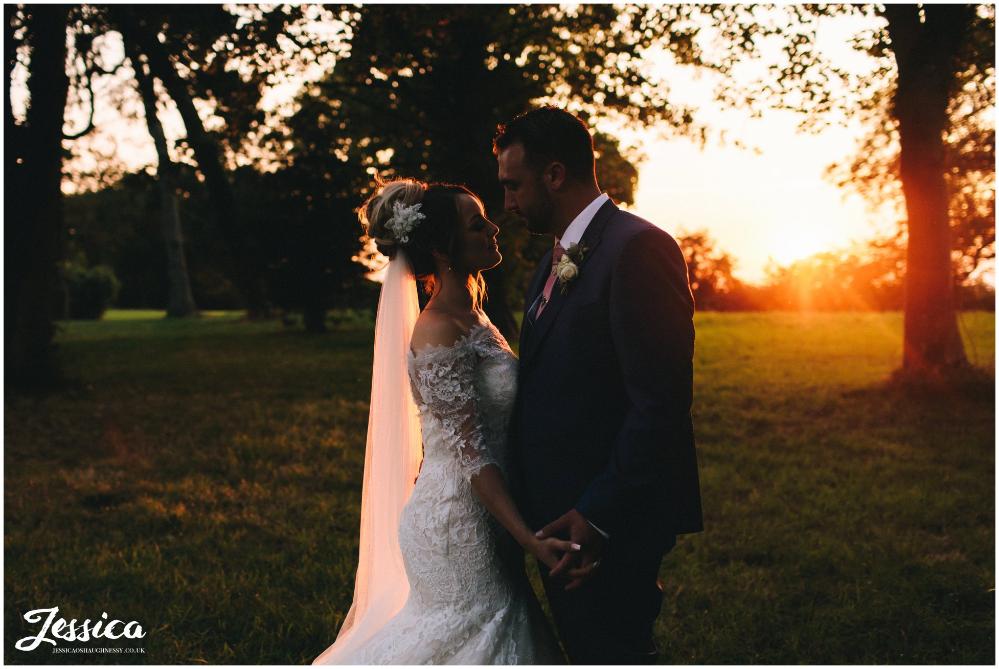 the couple hold hands as the sun goes down