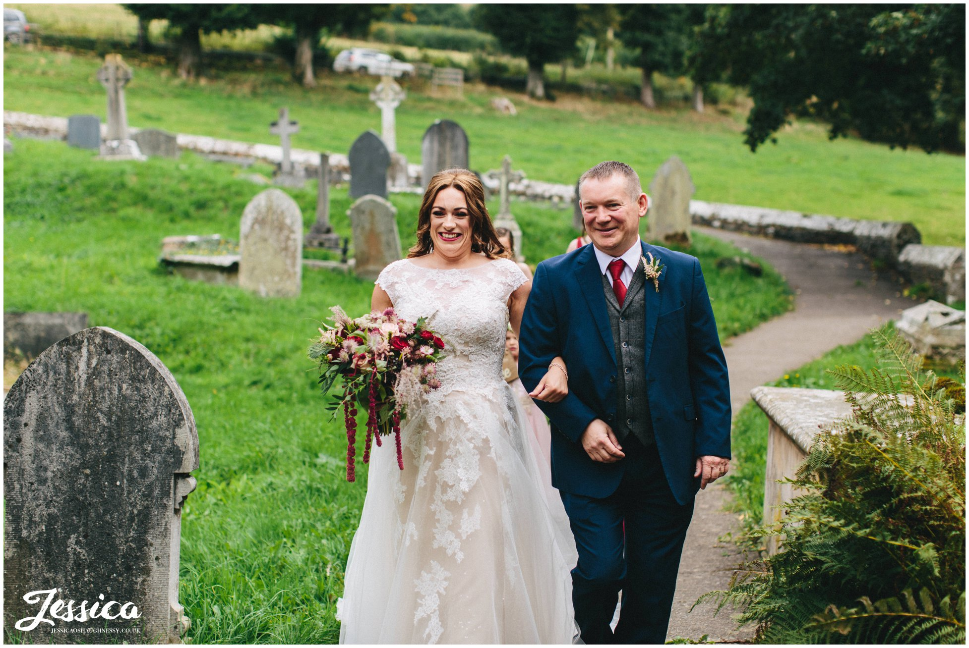 the bride and her father walk to the church entrance