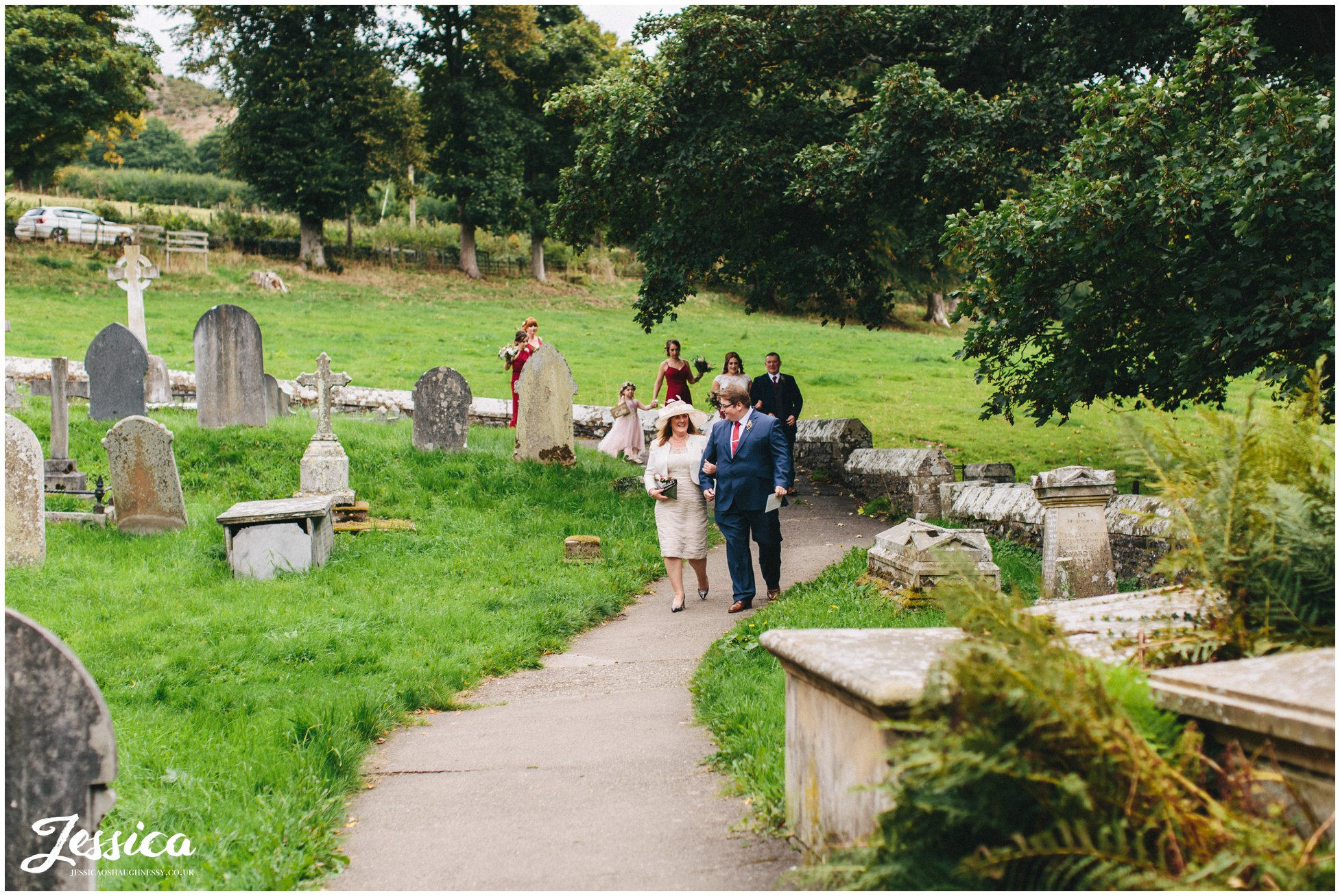 the bridal party walk down the church path