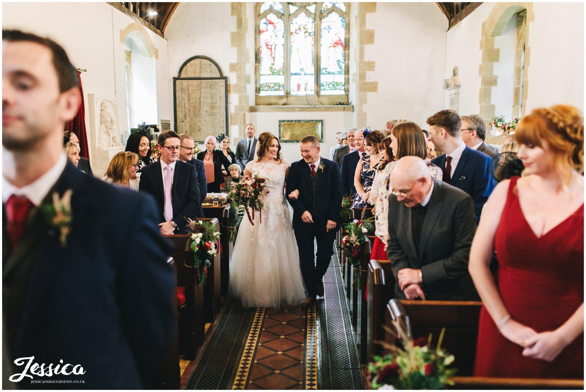 the bride walks down Llantysilio church aisle with her father