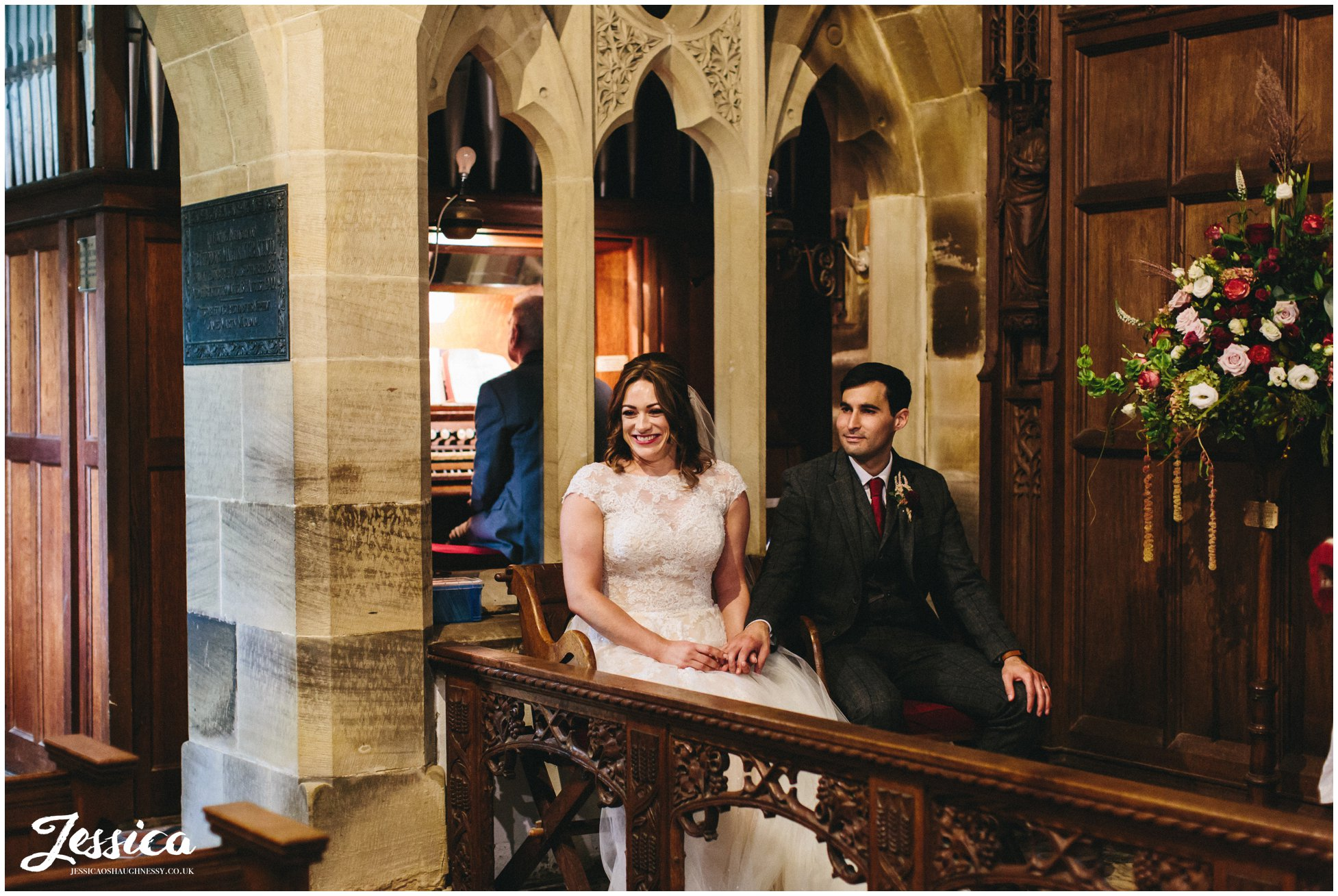 the couple sit during their wedding ceremony at Llantysilio church in north wales