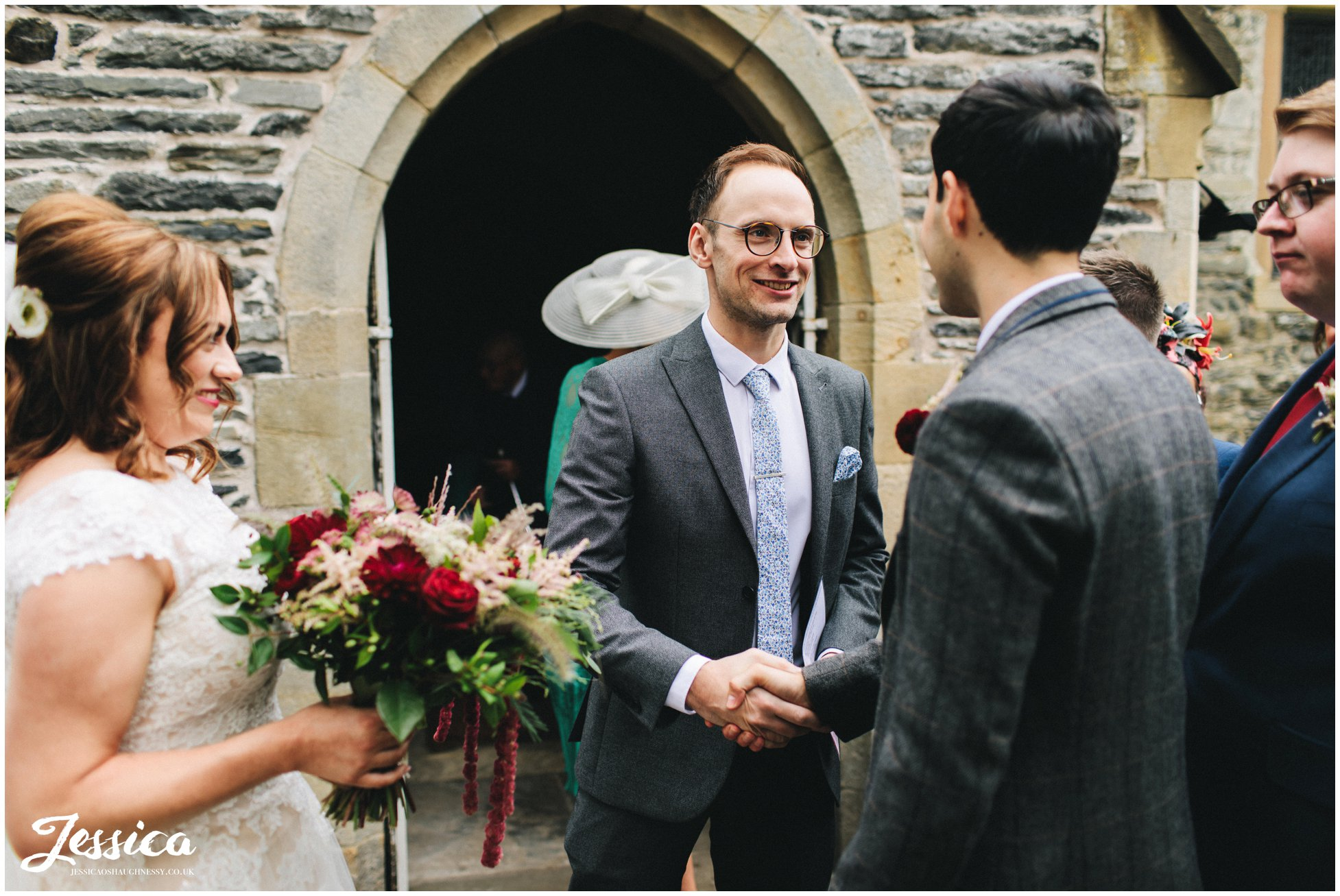 the brides brother shakes the grooms hand