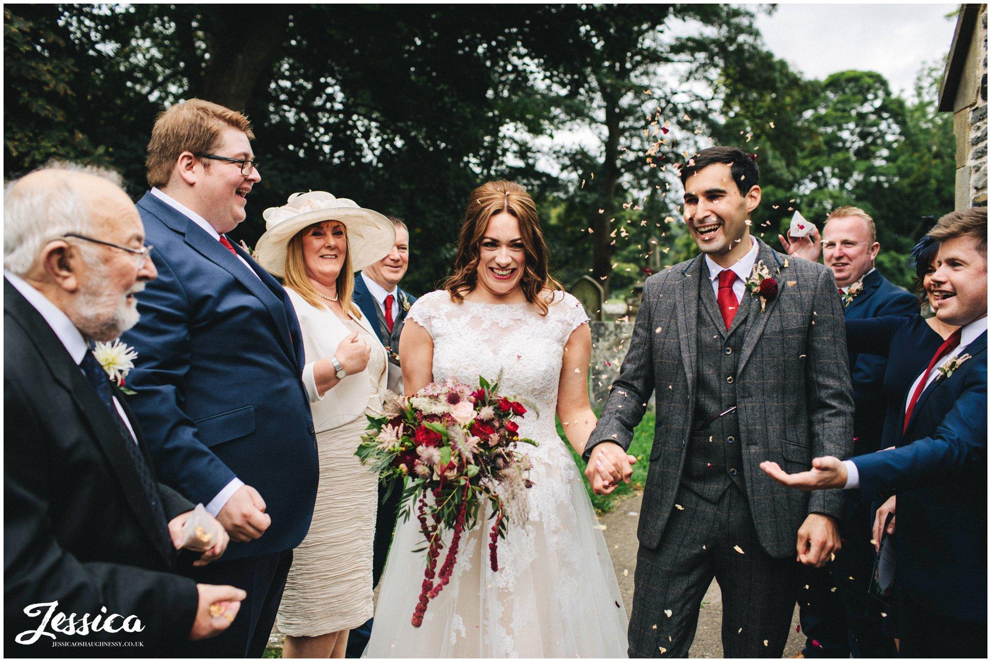 the bride and groom walk through their confetti line