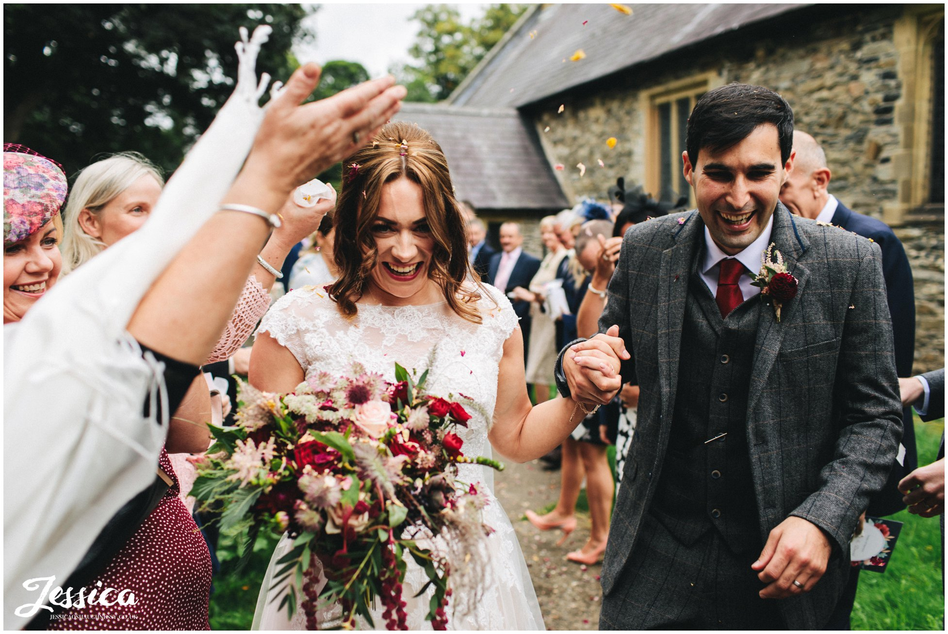 the couple are showered in confetti at Llantysilio church, north wales