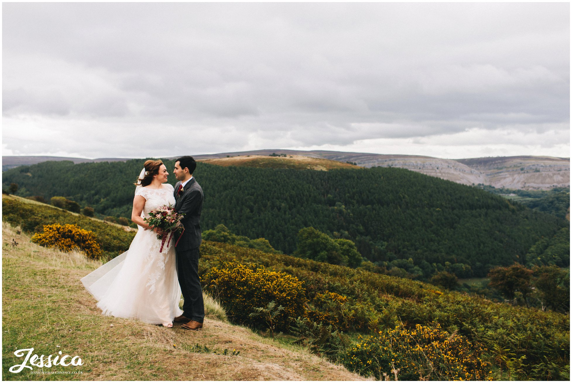 the newly wed's hold each other at the top of the welsh valleys