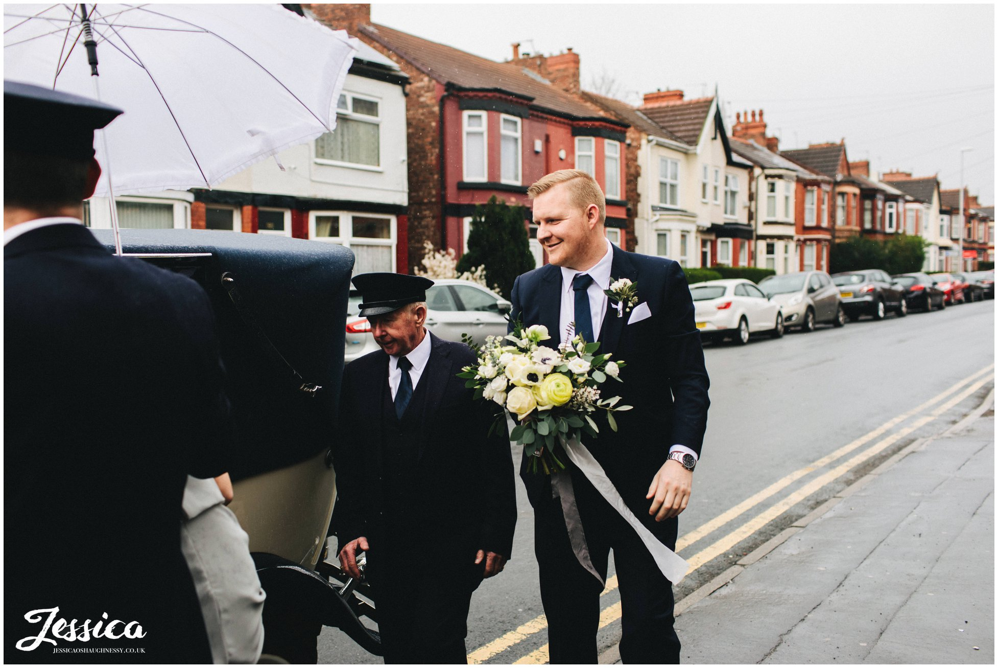 the brides brother holds her bouquet whilst she gets out the wedding car
