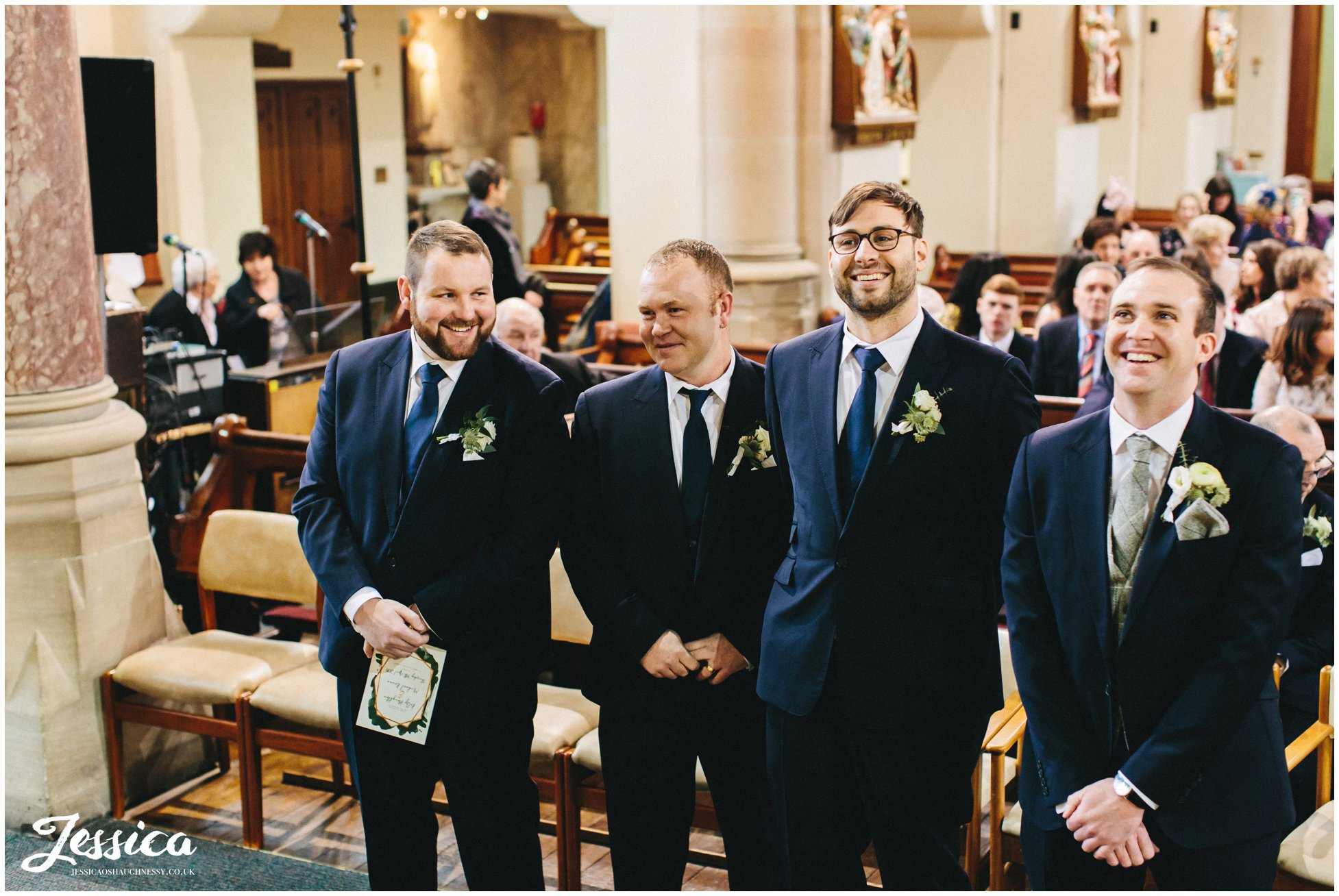 the groom & groomsmen laugh at the front of the church