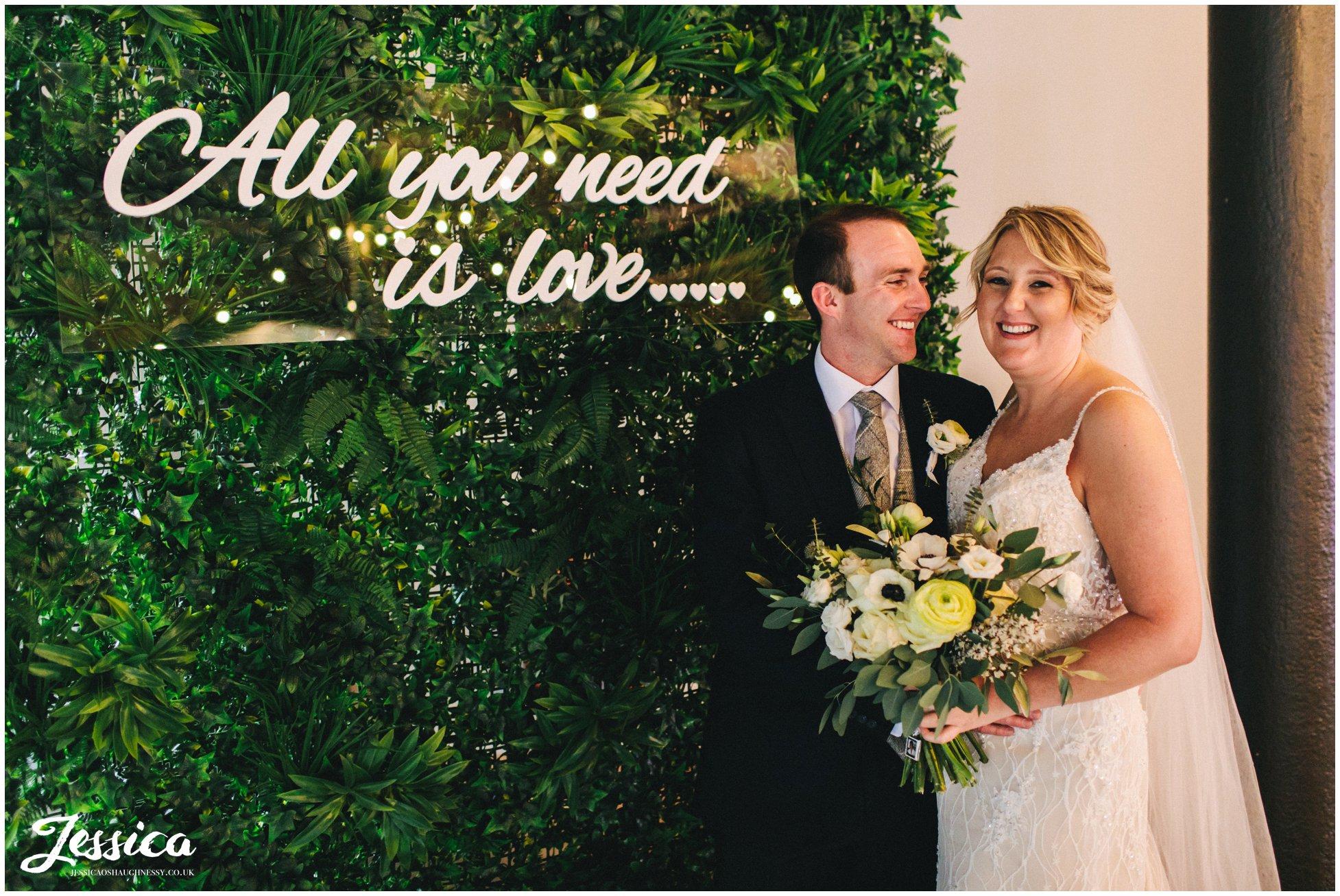 couple pose with botanical backdrop