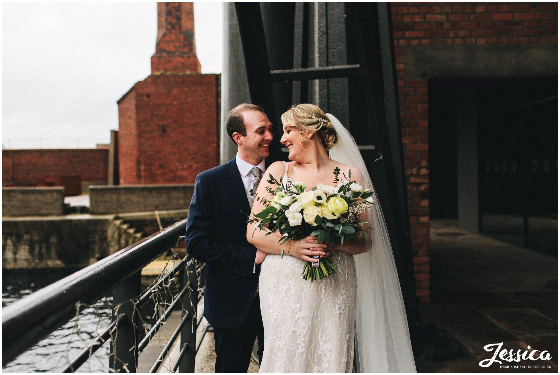 the bride & groom embrace along side liverpool docks