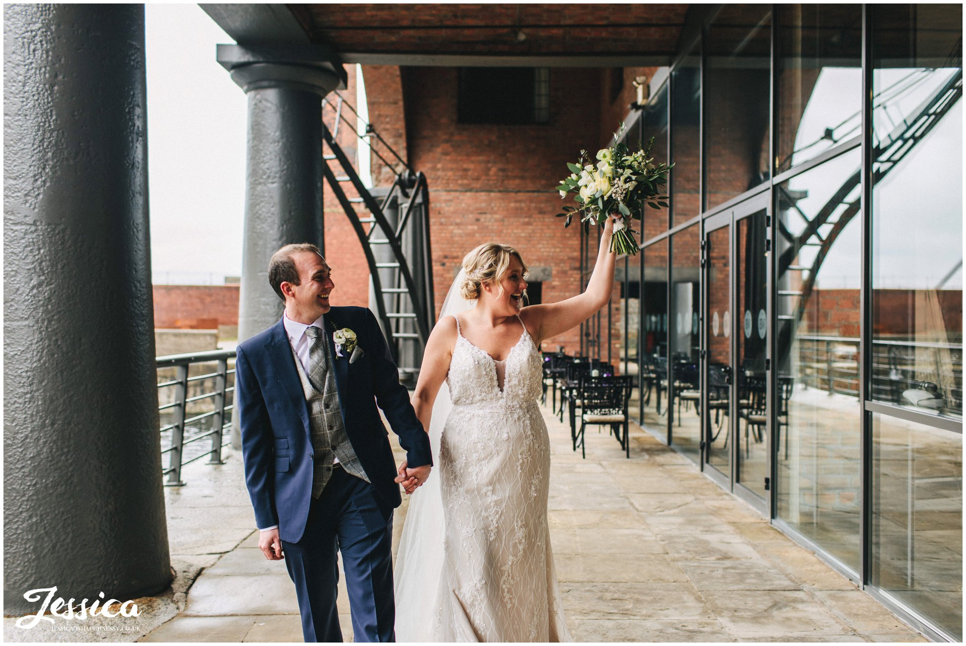 bride cheers to guests as they walk outside the liverpool venue