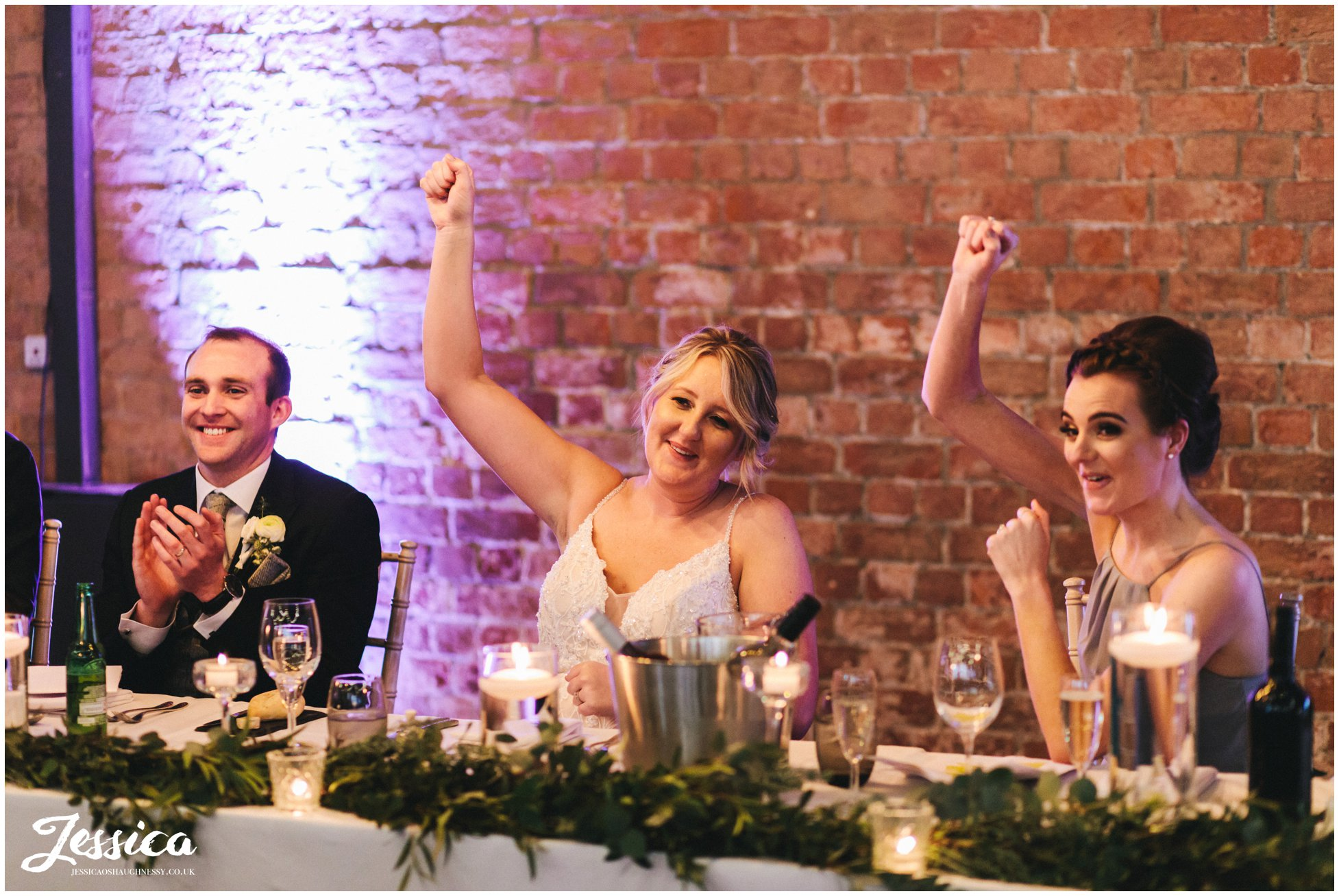 the bride & maid of honour cheer during the wedding speeches
