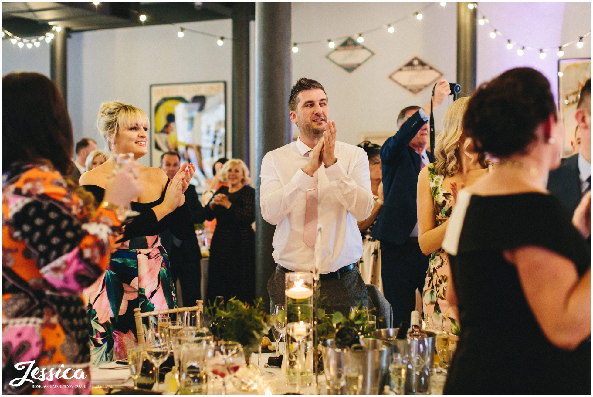 wedding guests clap as the couple enter