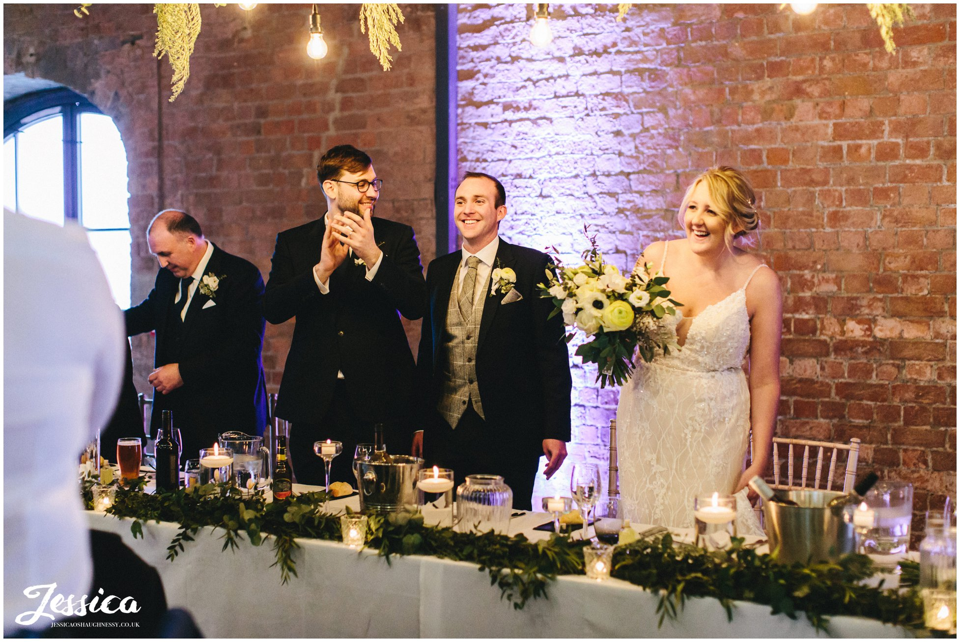the bride & groom take their places at the top table