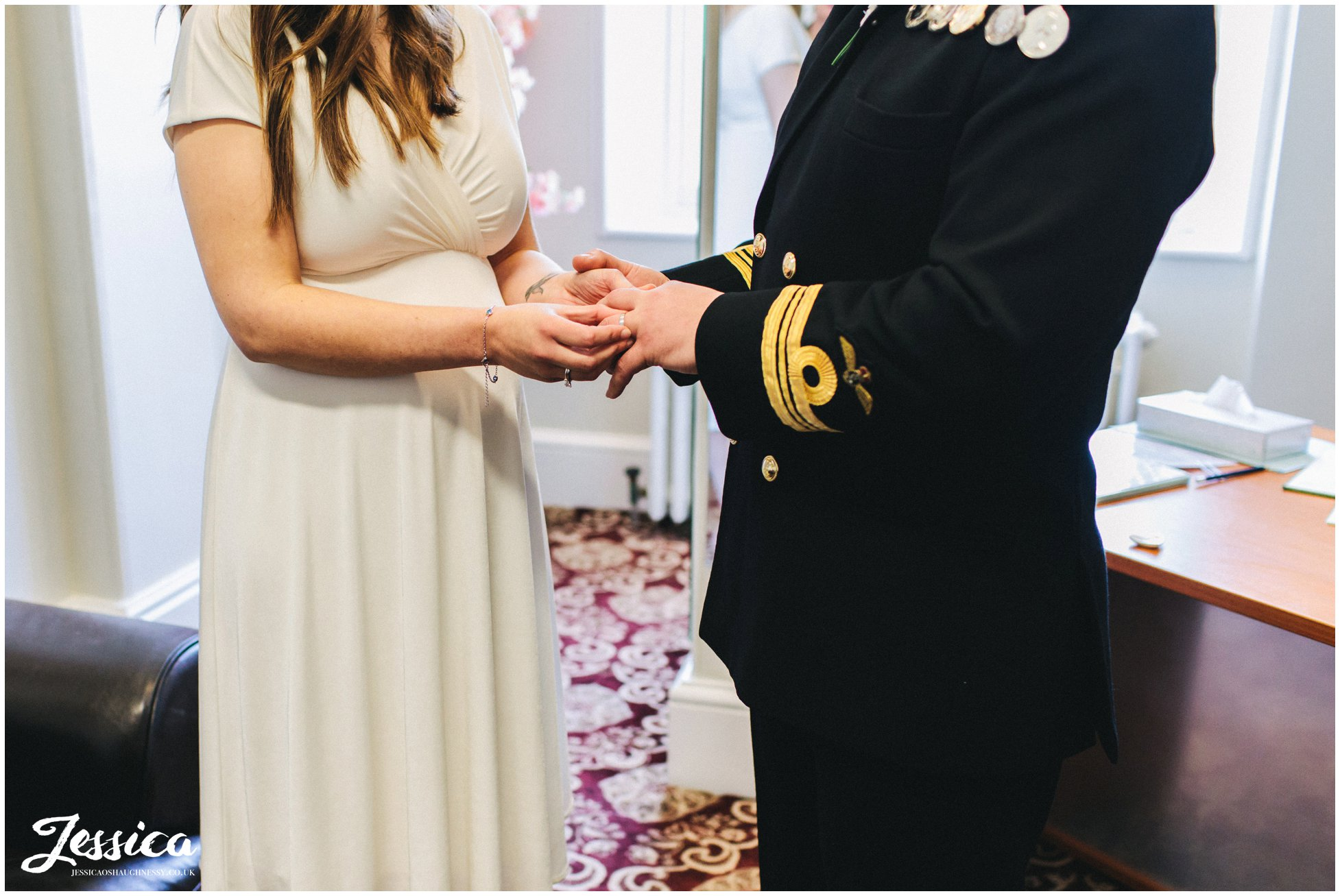 the bride places the ring on the grooms finger