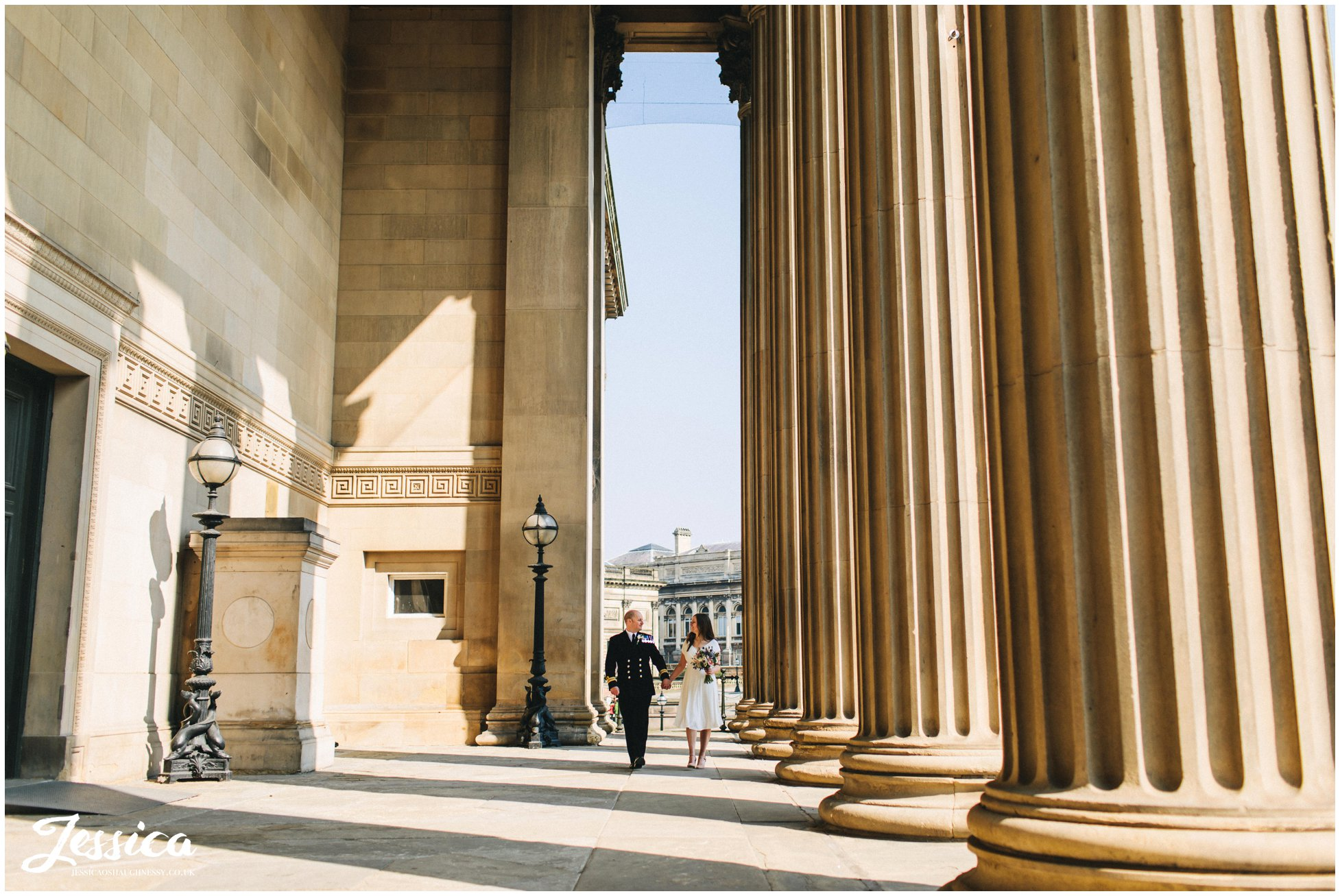 newly wed's walk between the columns after their elopement at st georges hall