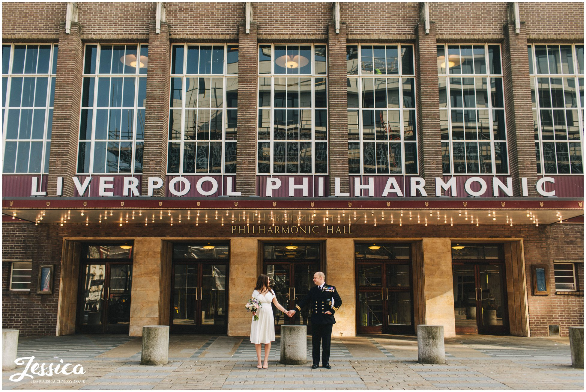 couple stand under the liverpool philharmonic