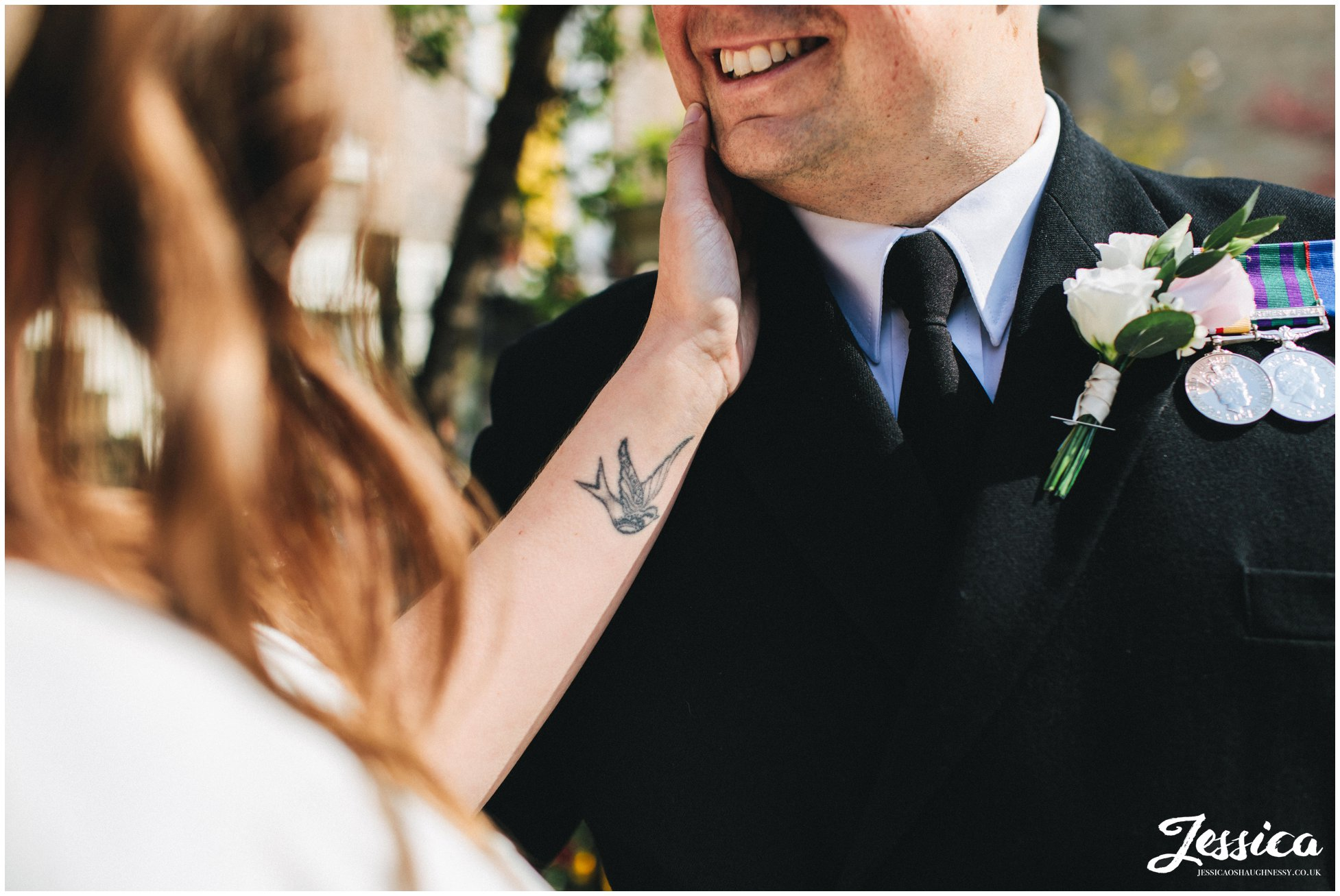 the bride holds her grooms face and shows of swallow tattoo